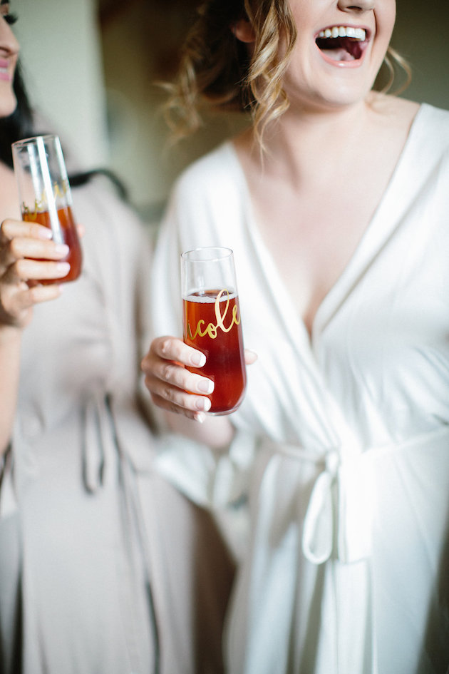 bride bellini in stemless champagne glass with her name on it in a white robe | Nicole + Luke | Villa Bellezza | Kristina Lorraine Photo12.jpg