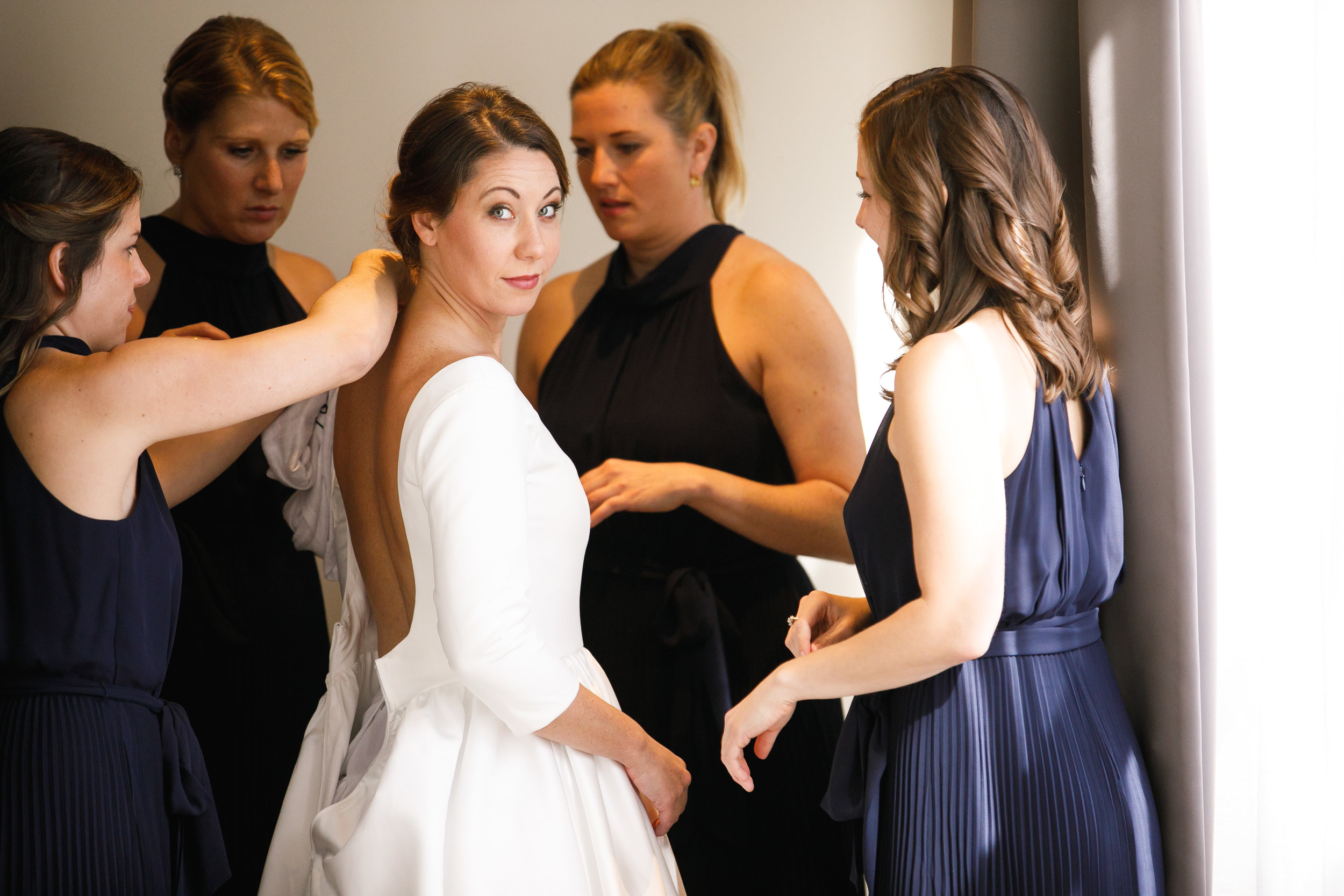 Brovado Wedding Photography | Machine Shop Minneapolis | Sixpence Events Day of Coordinating | getting ready shot of bride with her navy bridesmaids.jpg