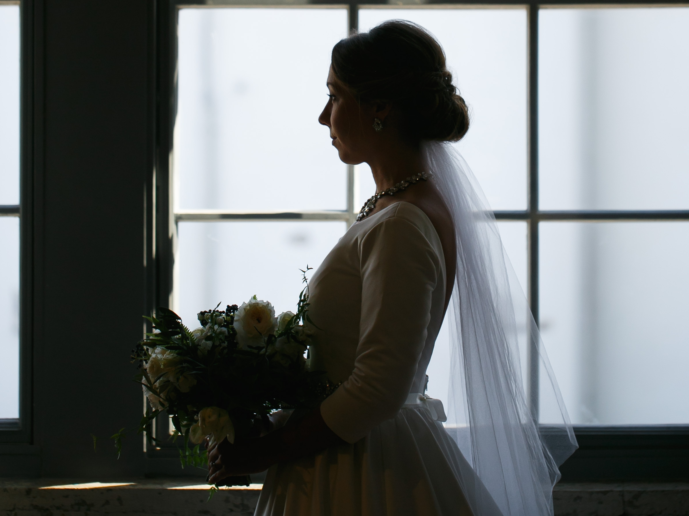 Brovado Wedding Photography | Machine Shop Minneapolis | Sixpence Events Day of Coordinating |bride silhouette in front of the windows.jpg