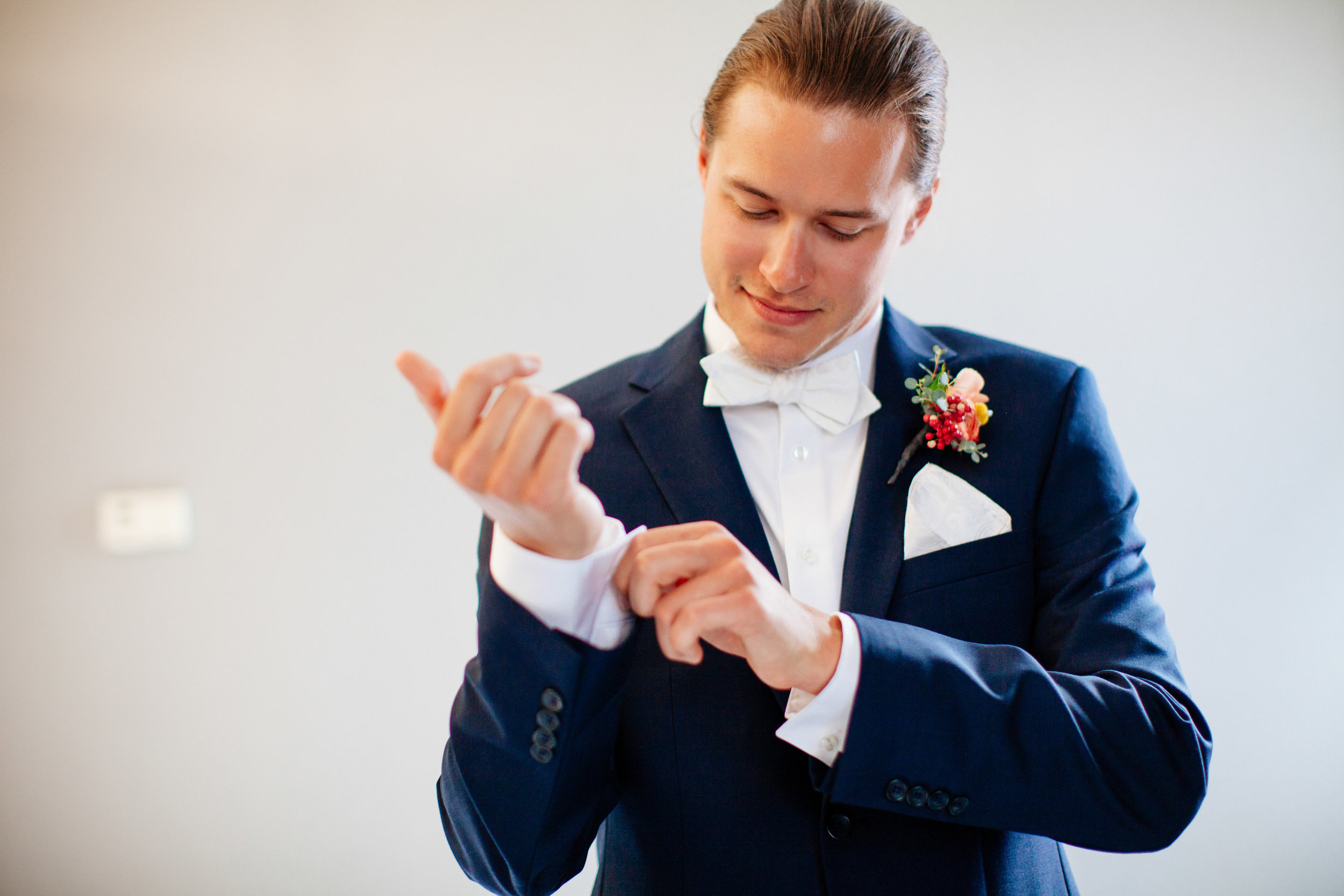 How to Capture Your Getting Ready Photos | Leah Fontaine Photography | Getting ready photos with groom in a navy suite with white bowtie and white pocket square