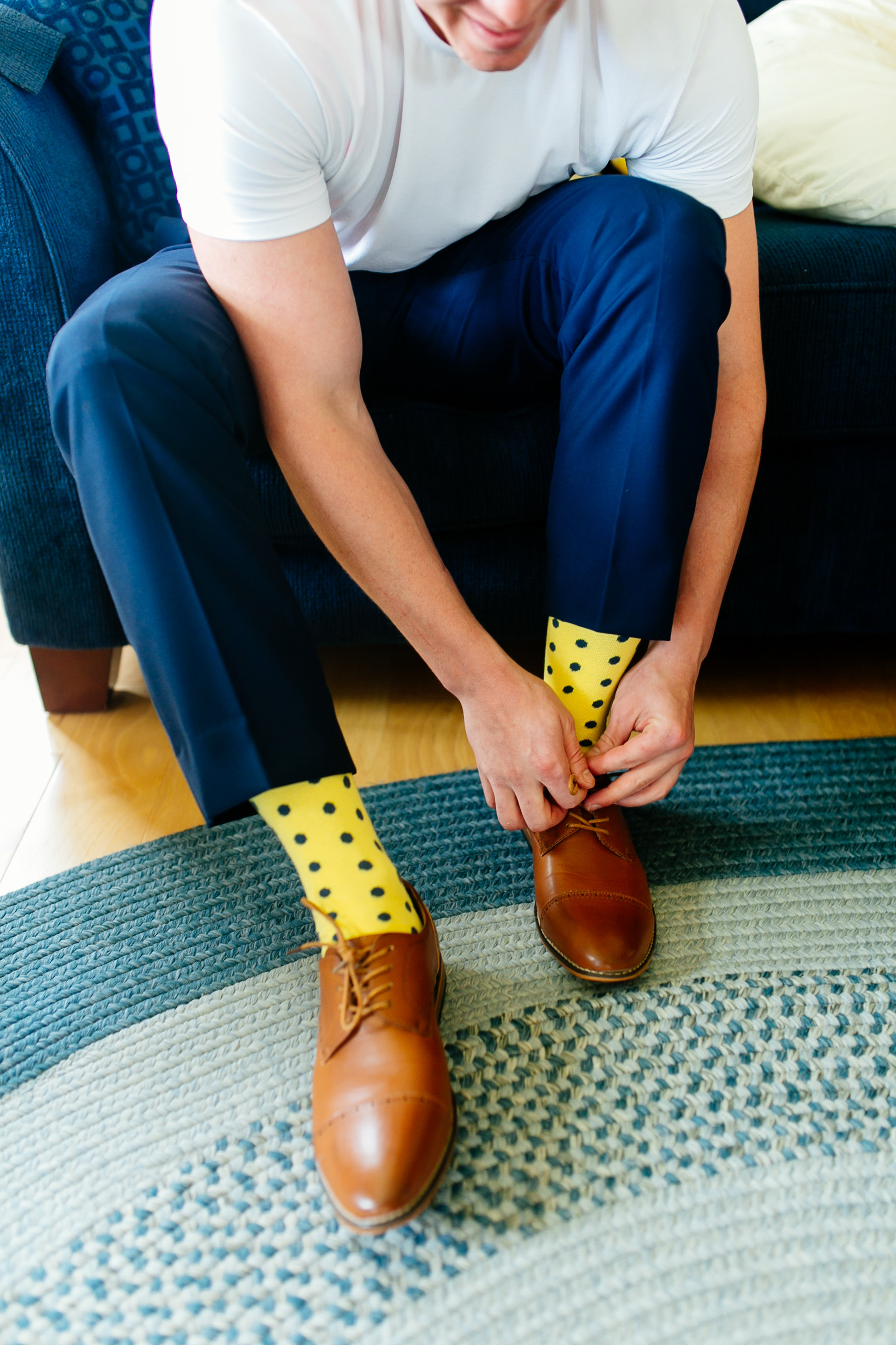 How to Capture Your Getting Ready Photos | Leah Fontaine Photography | Getting ready photos with groom putting on shoes with yellow polkadot socks