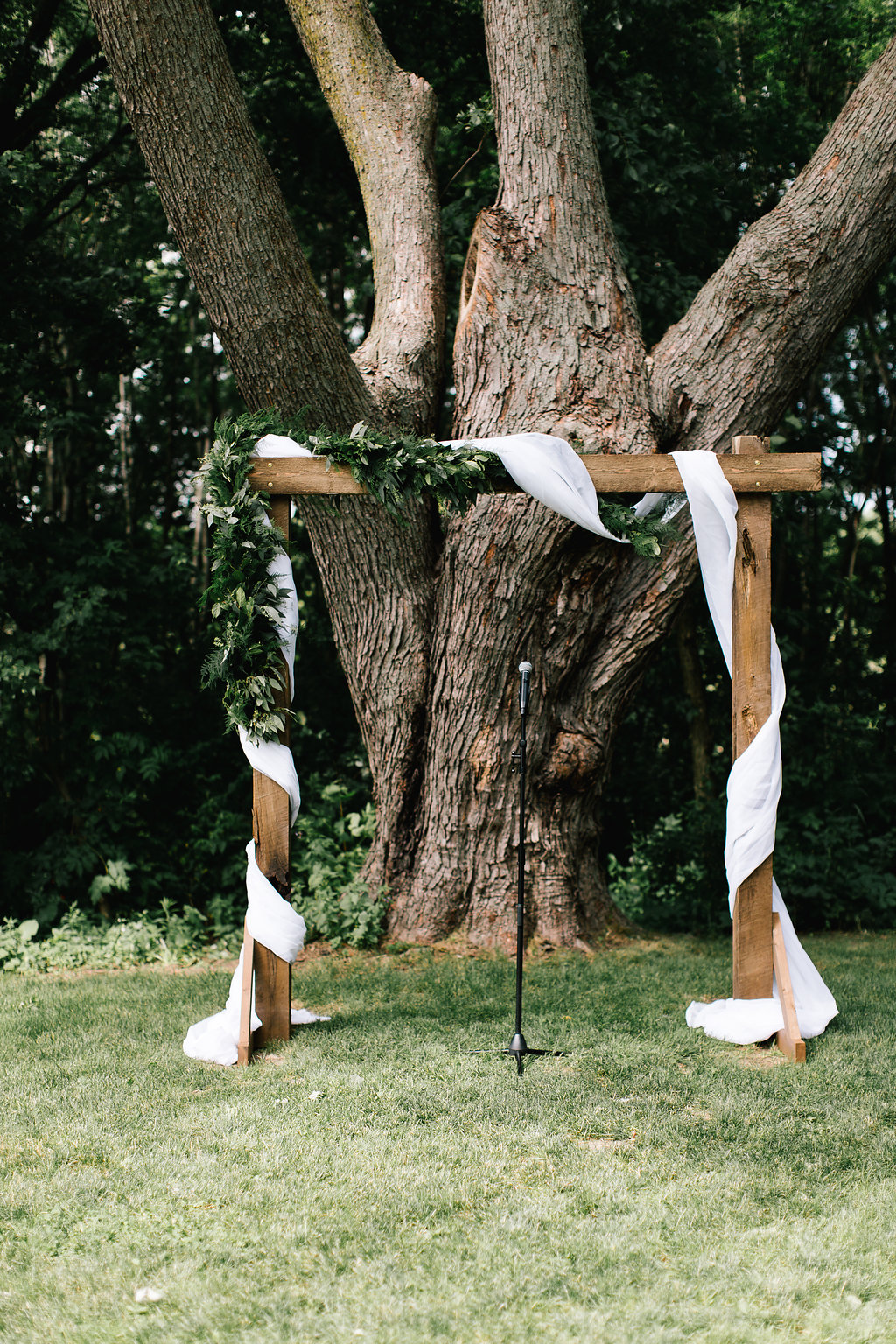 A Vintage Touch weddings ceremony arbor decor with draping in front of a large tree | barn wedding at Bloom Lake Barn | Photo by Allison Hopperstad | day of coordinating by Sixpence Events