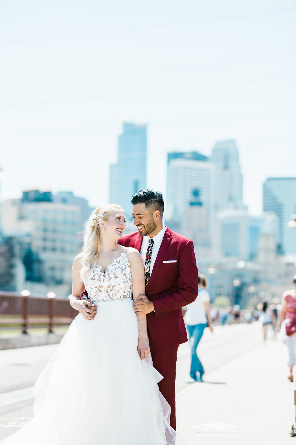 Marvin + Eloise | Hayley Paige dress and groom in red suit with floral tie | groom with a beard | Minneapolis skyscape | white pocket square | Aaron T Photo | Sixpence Events
