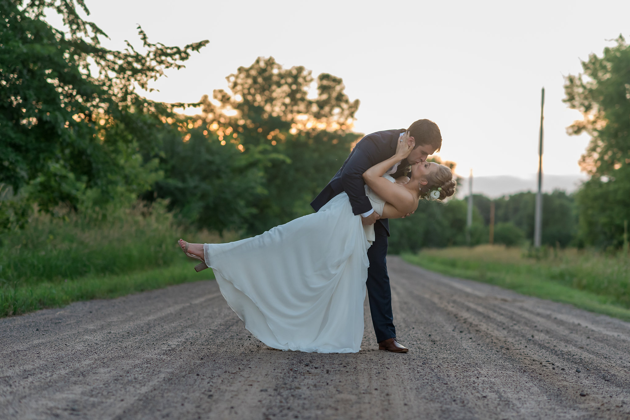 Carrie and Dave Married at Bloom Lake Barn // Kelly Birch Photography // dip kiss on a dirt road during golden hour // Sixpence Events // Minnesota barn wedding