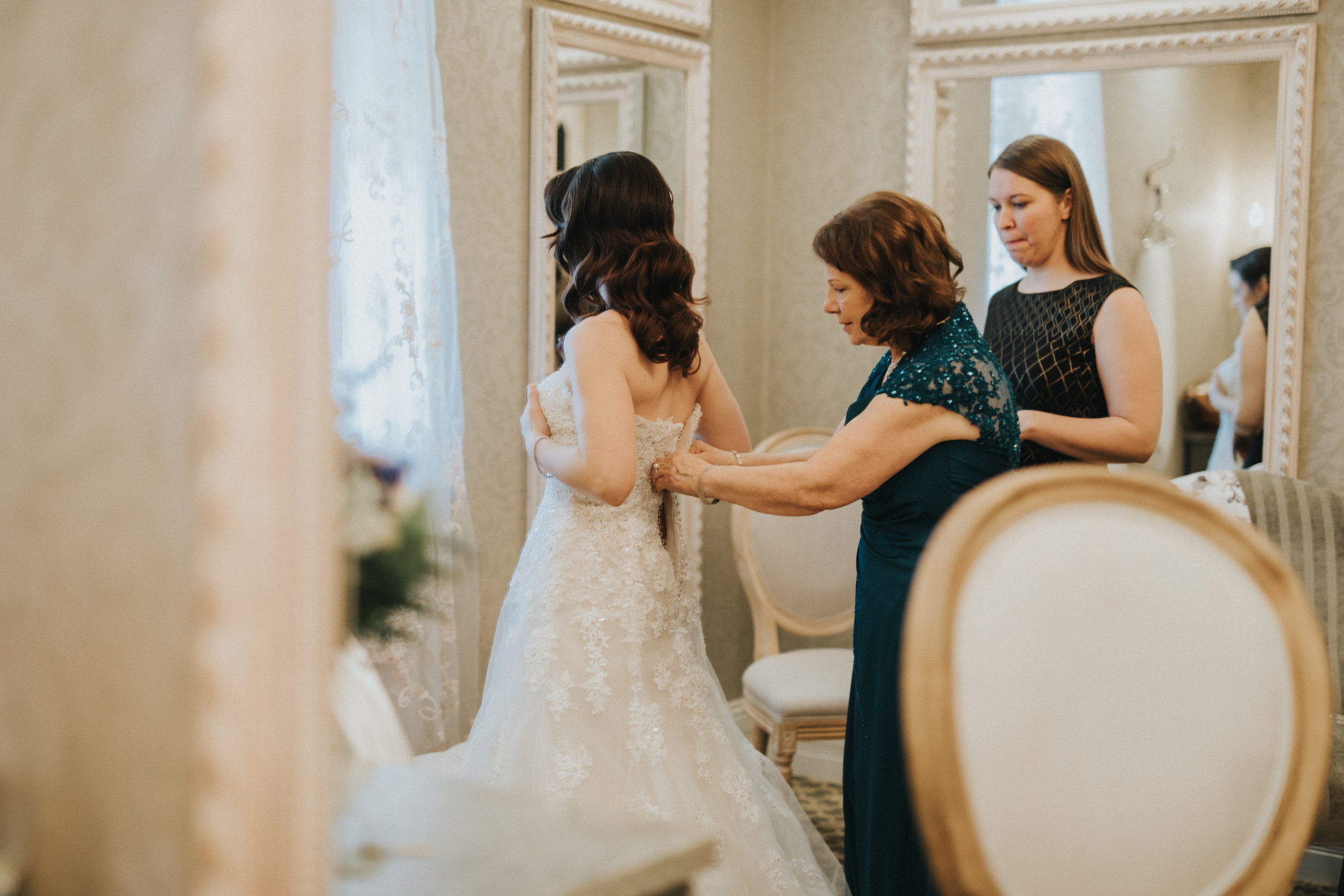 Bride getting into dress with mom at Nicollet Island Inn | Russell Heeter Photography :: Minneapolis wedding planner Sixpence Events :: Nicollet Island Pavilion :: april wedding in Minnesota.jpg