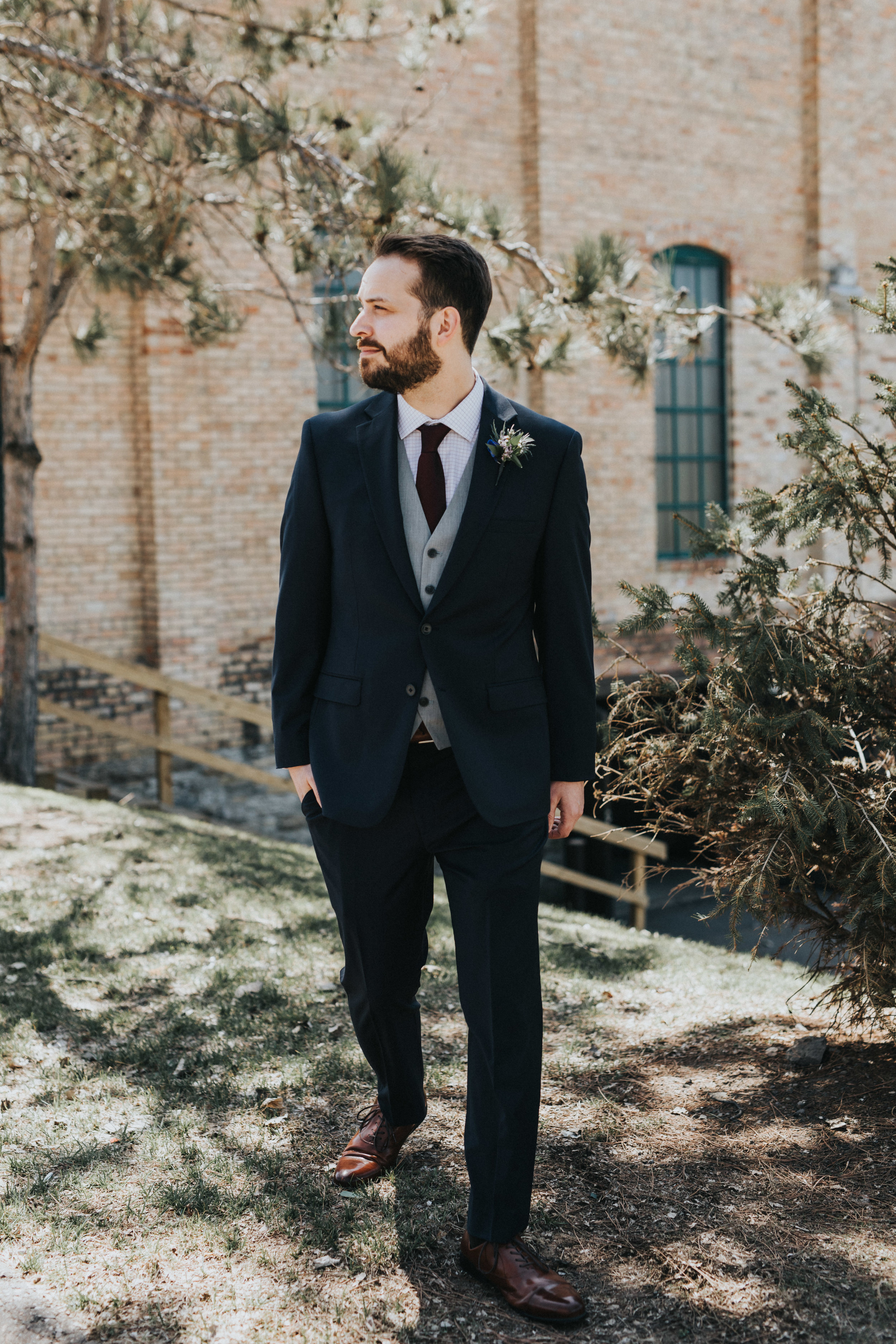 groom in navy suit with burgundy tie and gray vest | Russell Heeter Photography :: Minneapolis wedding planner Sixpence Events :: Nicollet Island Pavilion :: april wedding in Minnesota.jpg