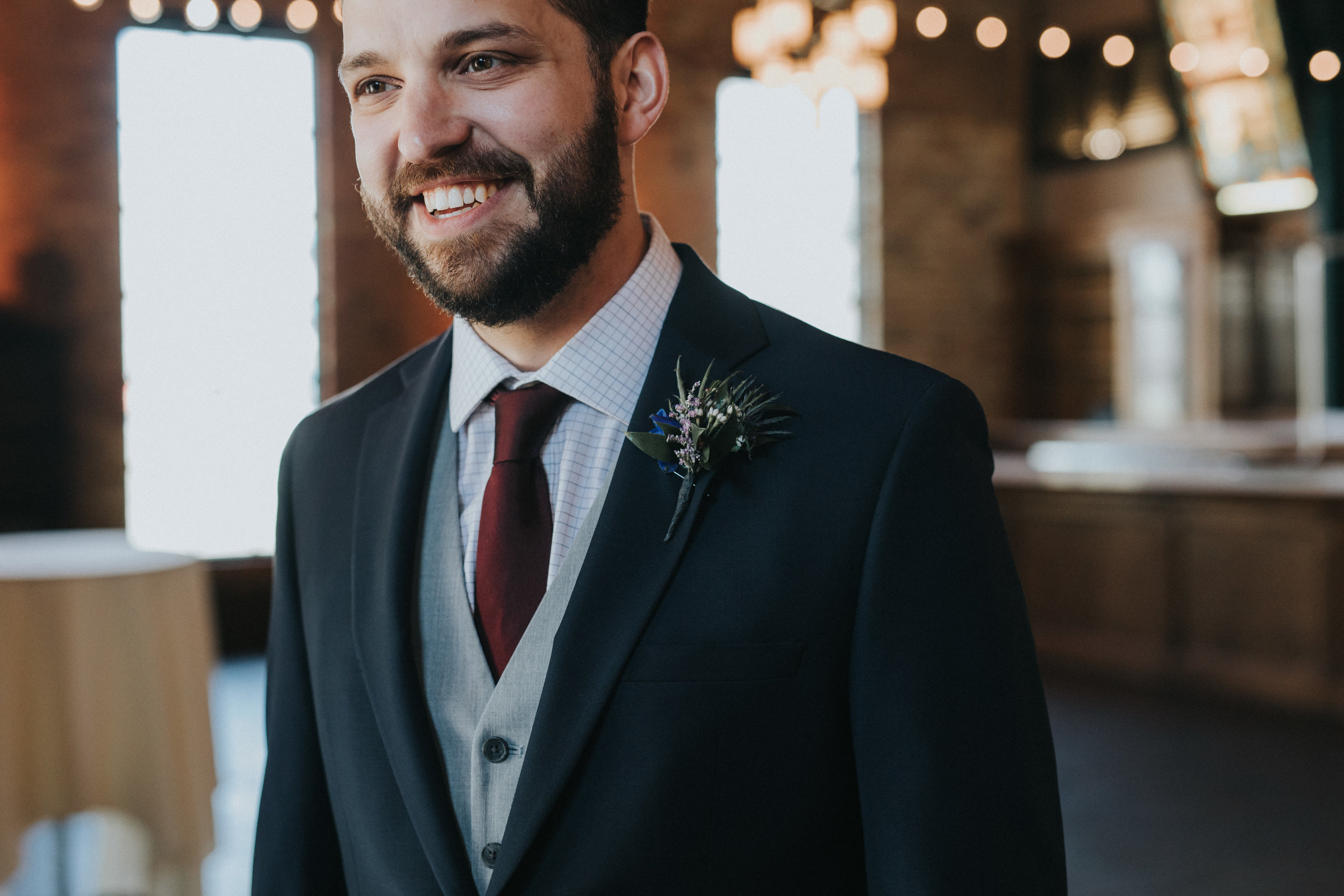 blue thistle boutonniere, groom with beard, groom in navy with gray vest and burgundy tie | Russell Heeter Photography :: Minneapolis wedding planner Sixpence Events :: Nicollet Island Pavilion :: april wedding in Minnesota.jpg