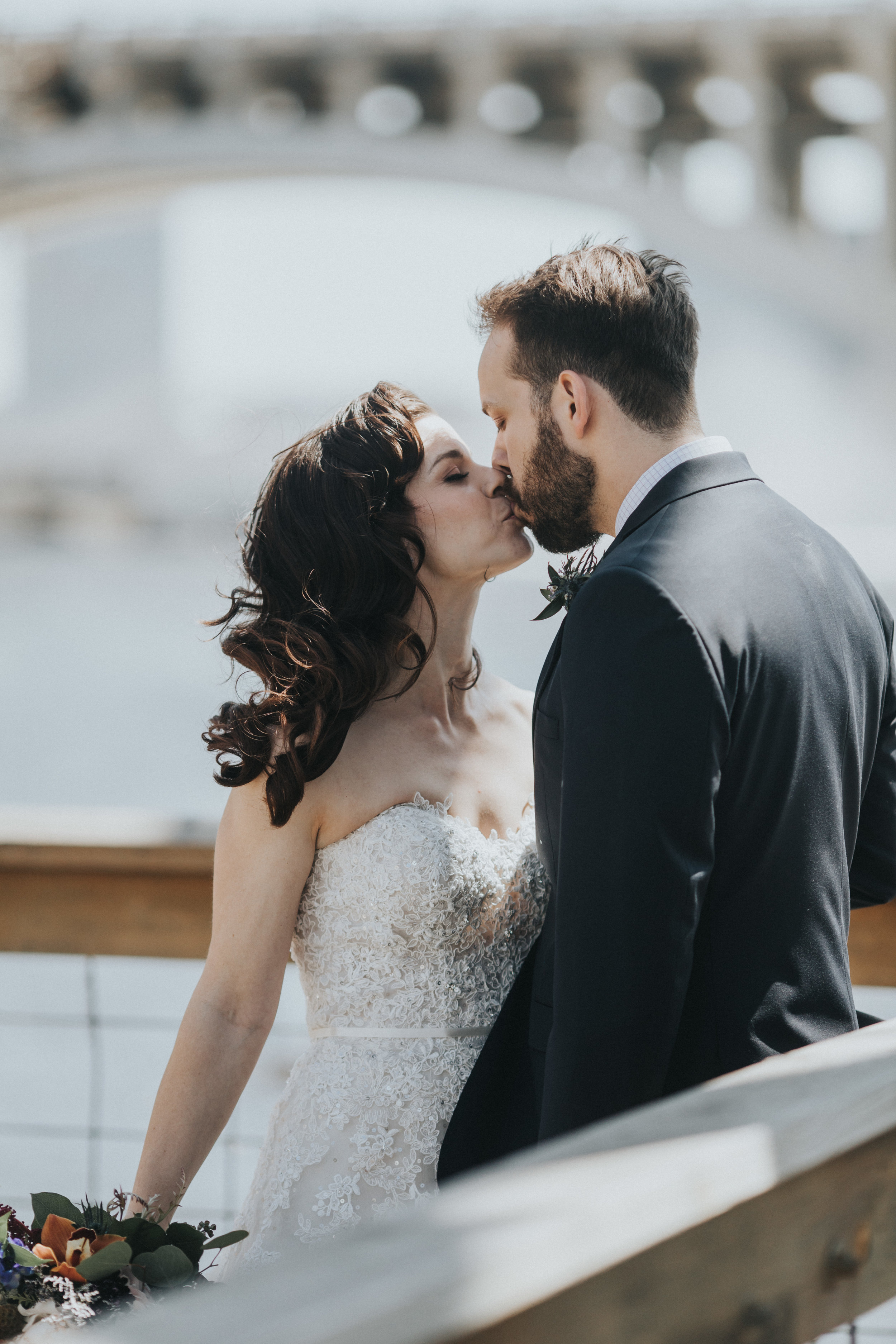 kiss on the deck at Nicollet Island | Russell Heeter Photography :: Minneapolis wedding planner Sixpence Events :: Nicollet Island Pavilion :: april wedding in Minnesota.jpg
