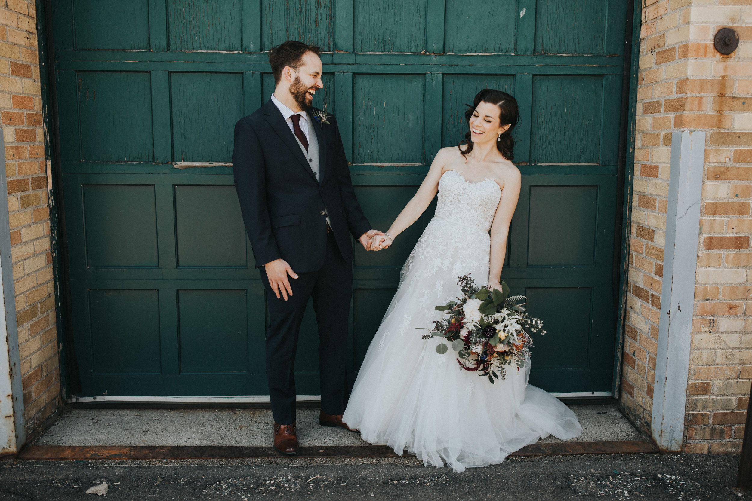 green door at Nicollet Island | laughing and holding hands | Russell Heeter Photography :: Minneapolis wedding planner Sixpence Events :: Nicollet Island Pavilion :: april wedding in Minnesota.jpg