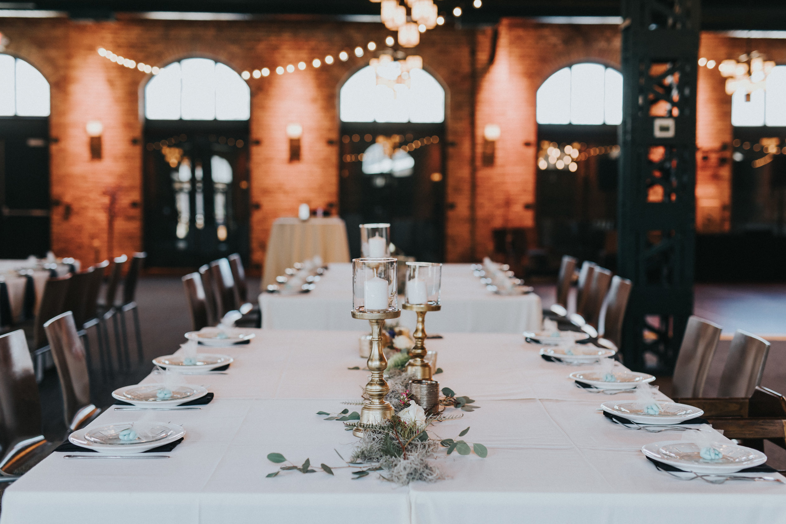 moss table runner, gold pillar candles, blue chocolate almonds guest favors | Russell Heeter Photography :: Minneapolis wedding planner Sixpence Events :: Nicollet Island Pavilion :: april wedding in Minnesota.jpg