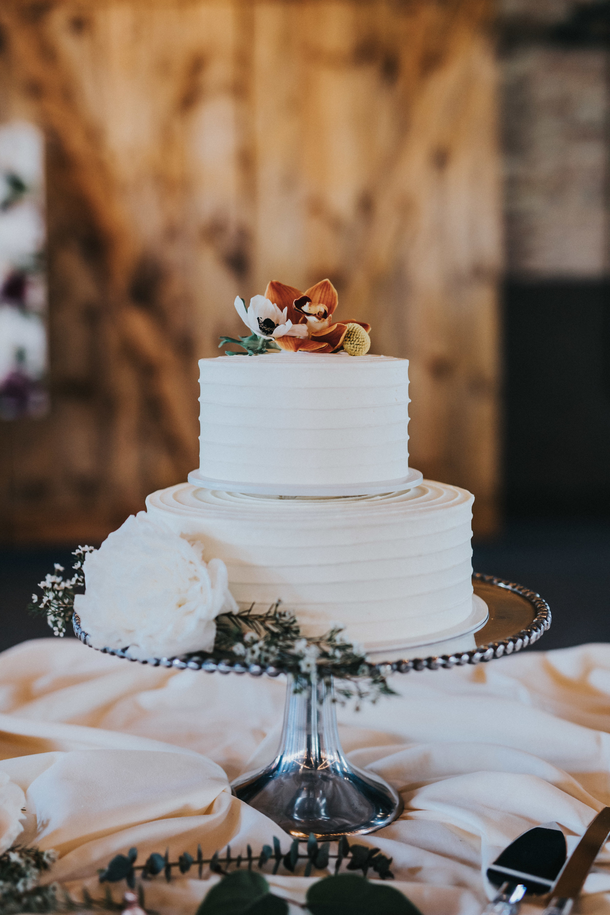 Buttercream tiramisu two tiered cake simple frosting with orchid and peony on top | Russell Heeter Photography :: Minneapolis wedding planner Sixpence Events :: Nicollet Island Pavilion :: april wedding in Minnesota.jpg