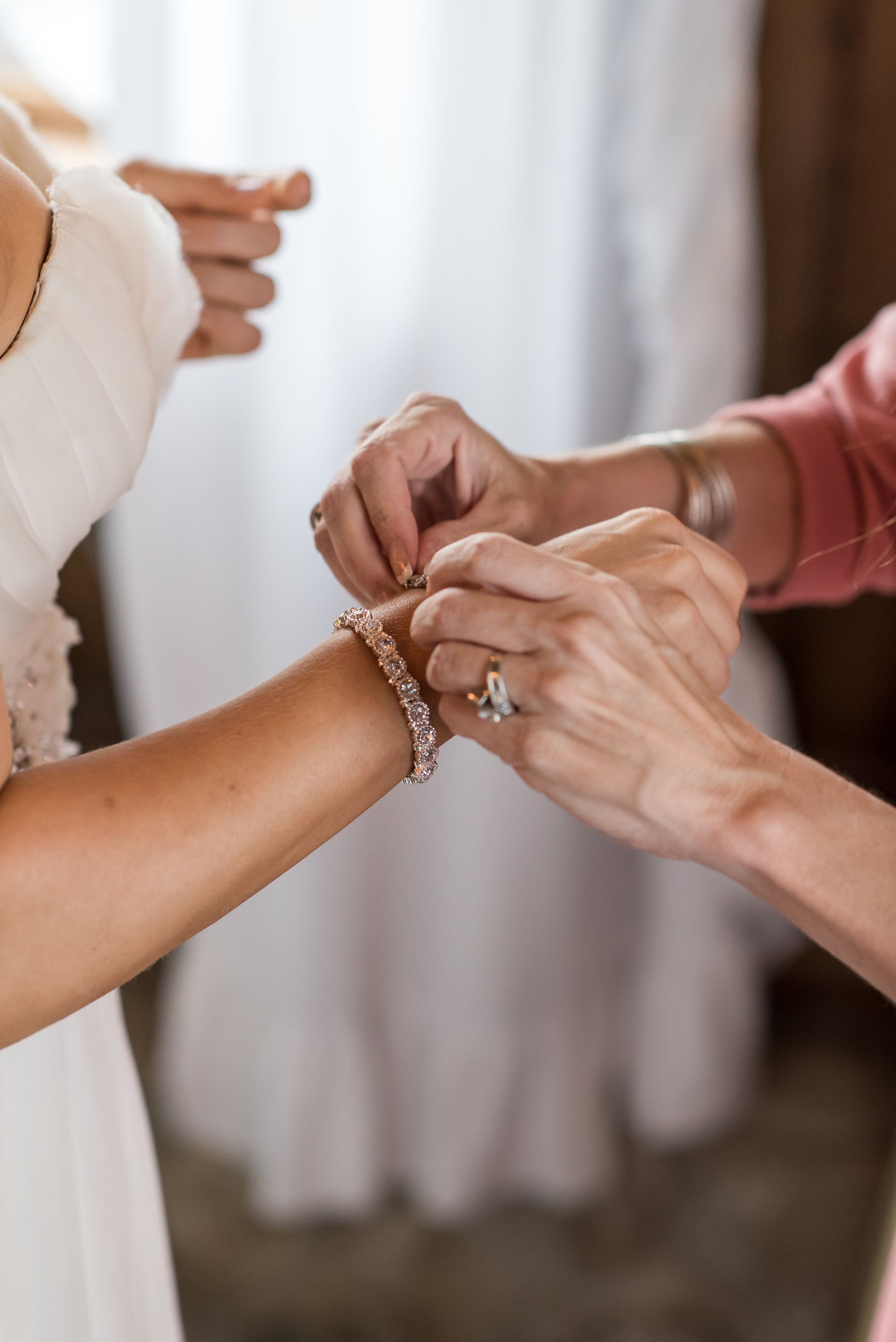 putting on bridal bracelet | Kelly Birch Photography :: Bloom Lake Barn :: Sixpence Events Minnesota wedding planner :: A Vintage Touch Weddings :: Brett Dorian.jpg