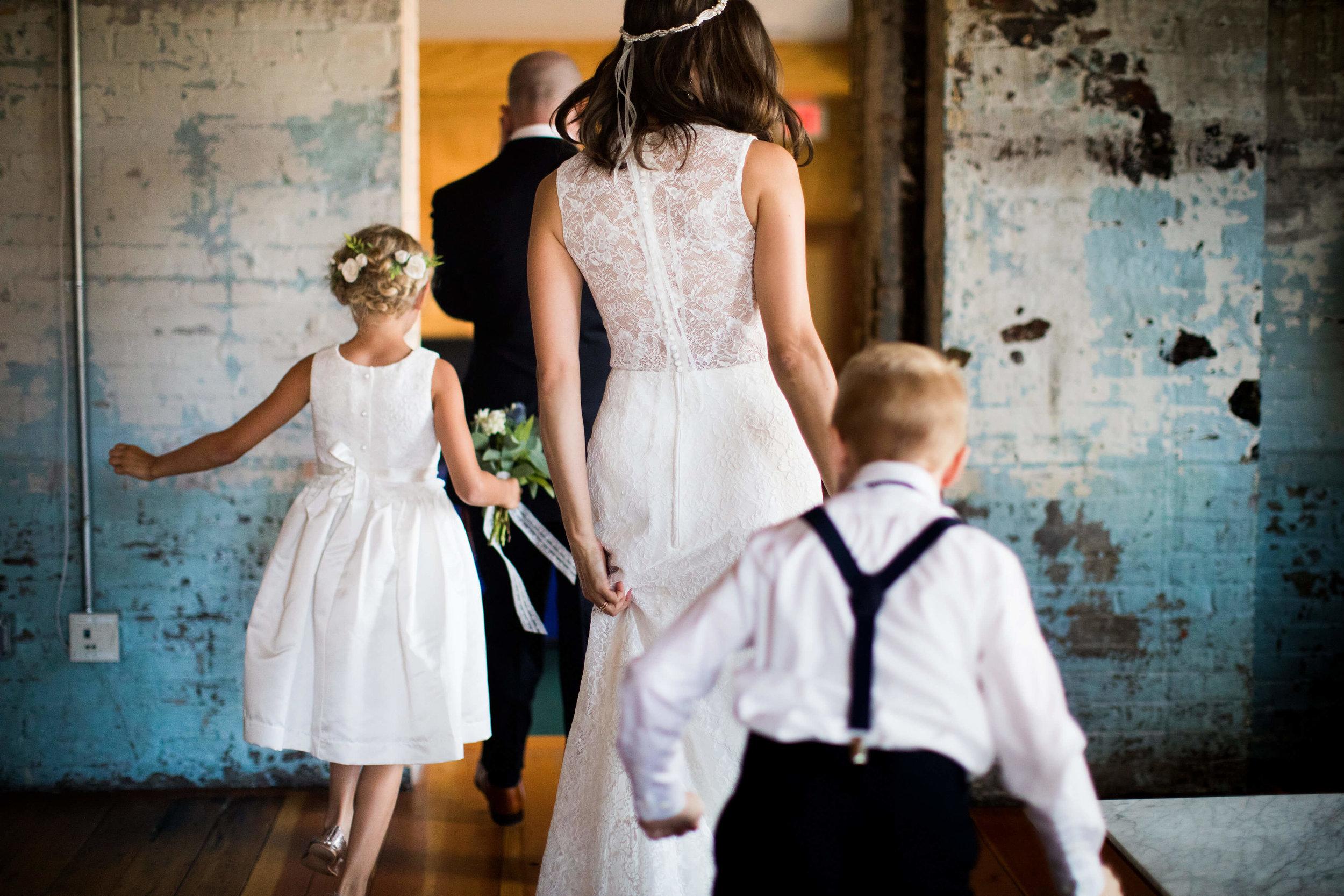 walking out for the wedding with ringbearer and flower girl | Minnesota wedding photographer Studio KH wedding dress details | wedding blog | Sixpence Events 70 Ways to Photograph Your Wedding Dress.jpg