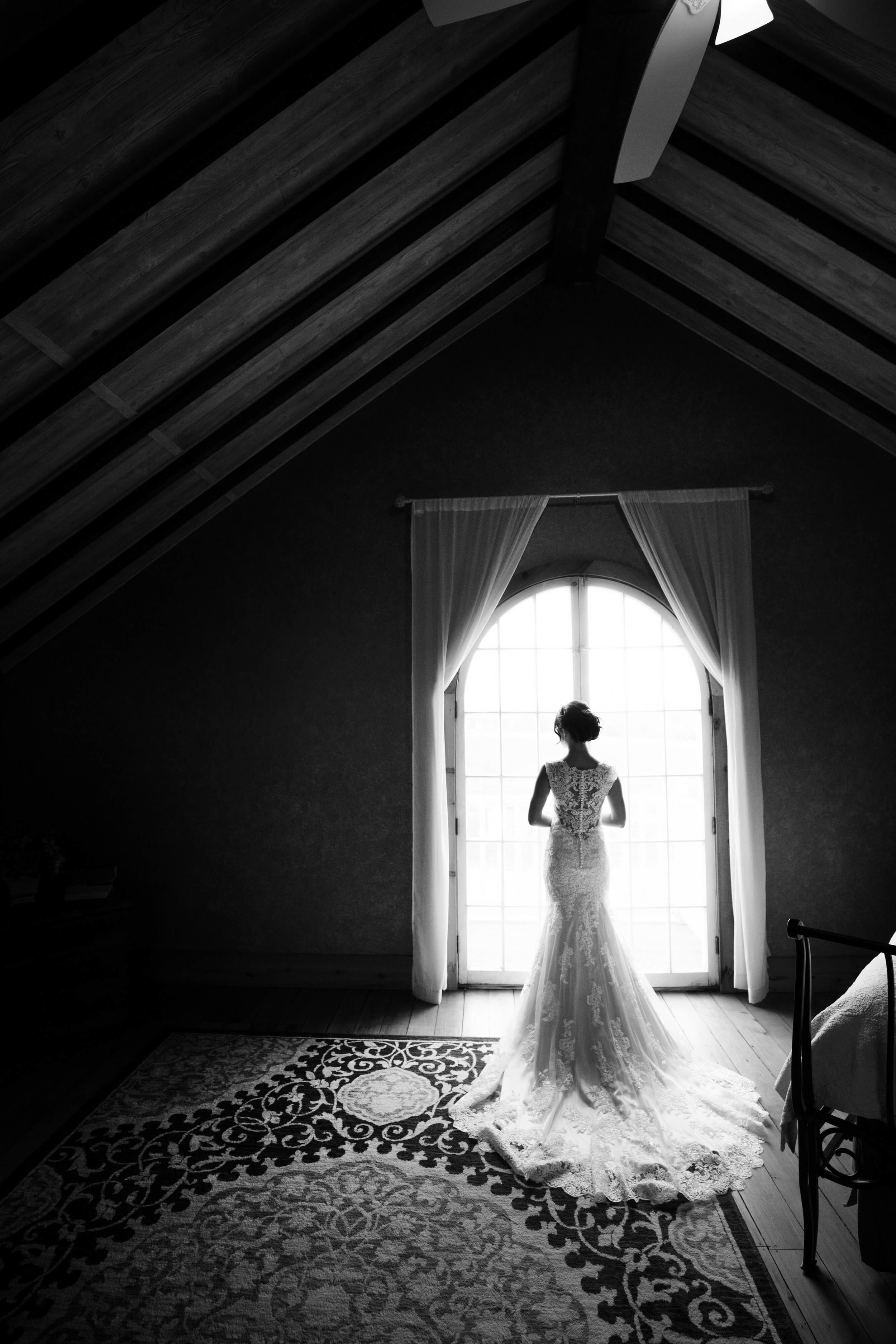 bride alone in the attic in front of the window - full train photo | Sixpence Events and Planning | Studio KH wedding