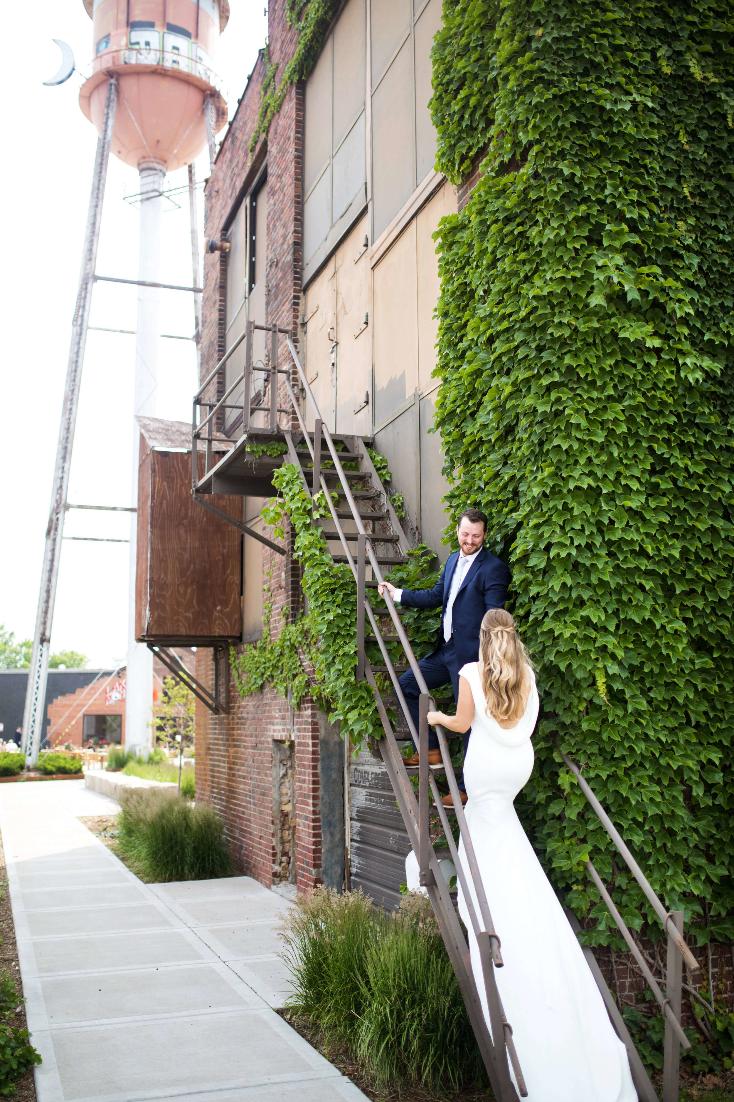 Studio KH wedding photographer | Sixpence Events and Planning, free wedding blog, free wedding help, free wedding advice | bride and groom walking up fire stairs with ivy at PAIKKA