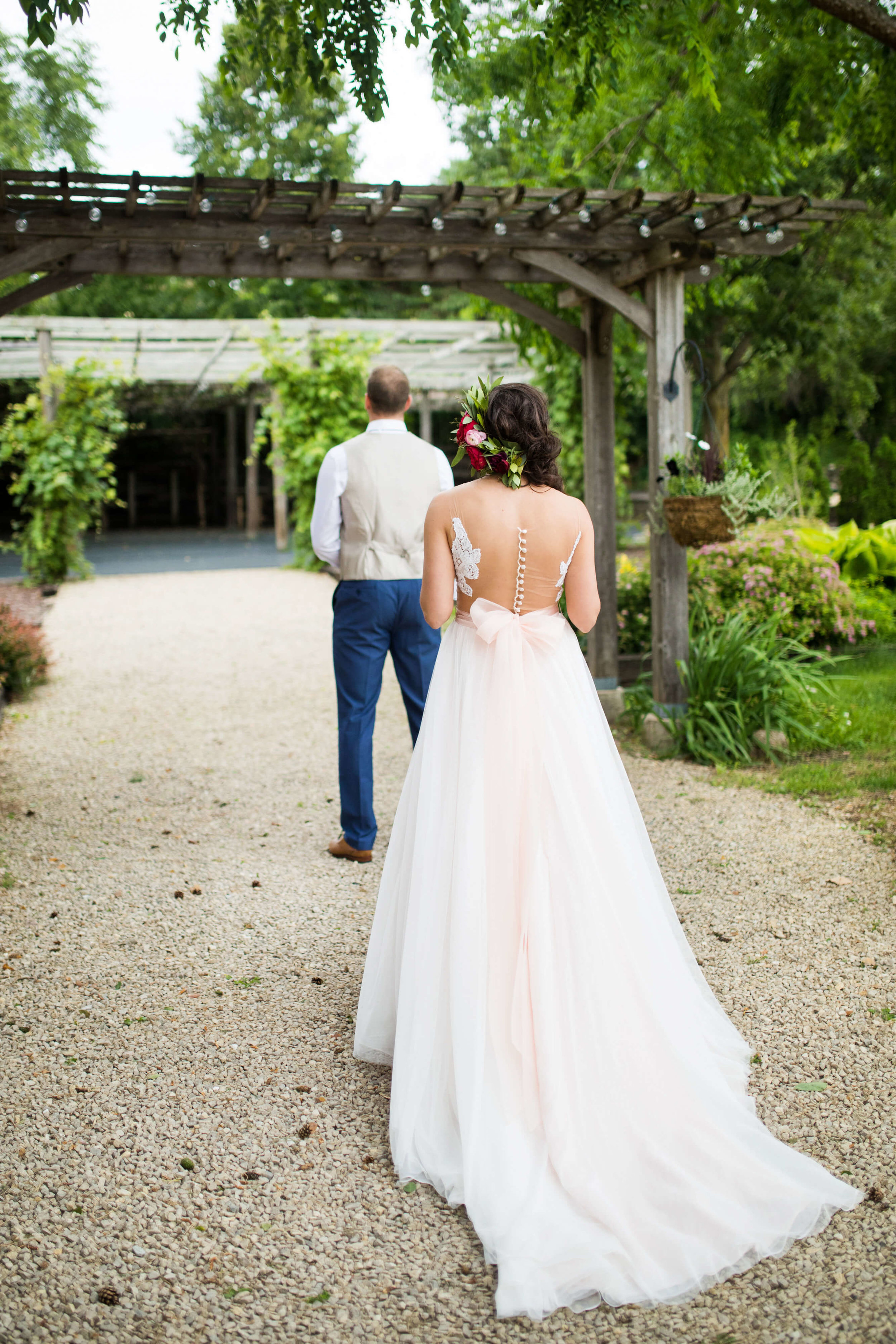 Studio KH wedding photographer | Sixpence Events and Planning, free wedding blog, free wedding help, free wedding advice |  bride walking to first look at Gardens of Castle Rock with sheer back  buttons showing | groom in taupe vest with navy pants