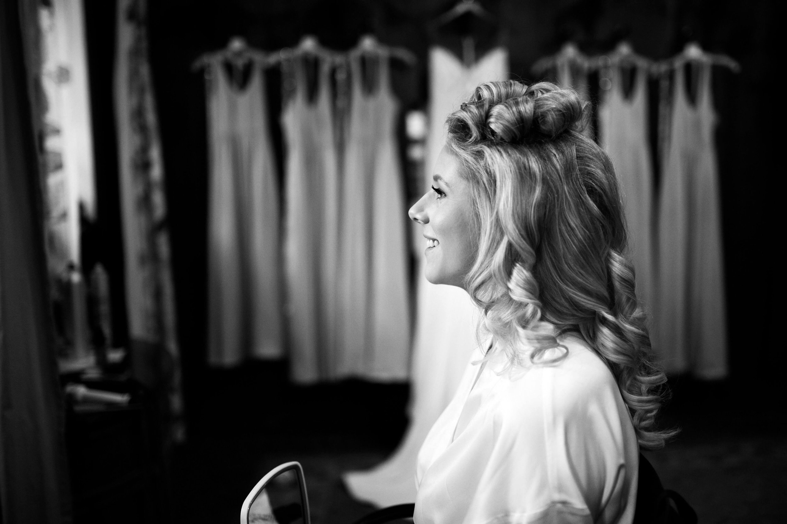 bride getting ready photo with dresses in the backdrop | Sixpence Events and Planning blog | Studio KH wedding photography