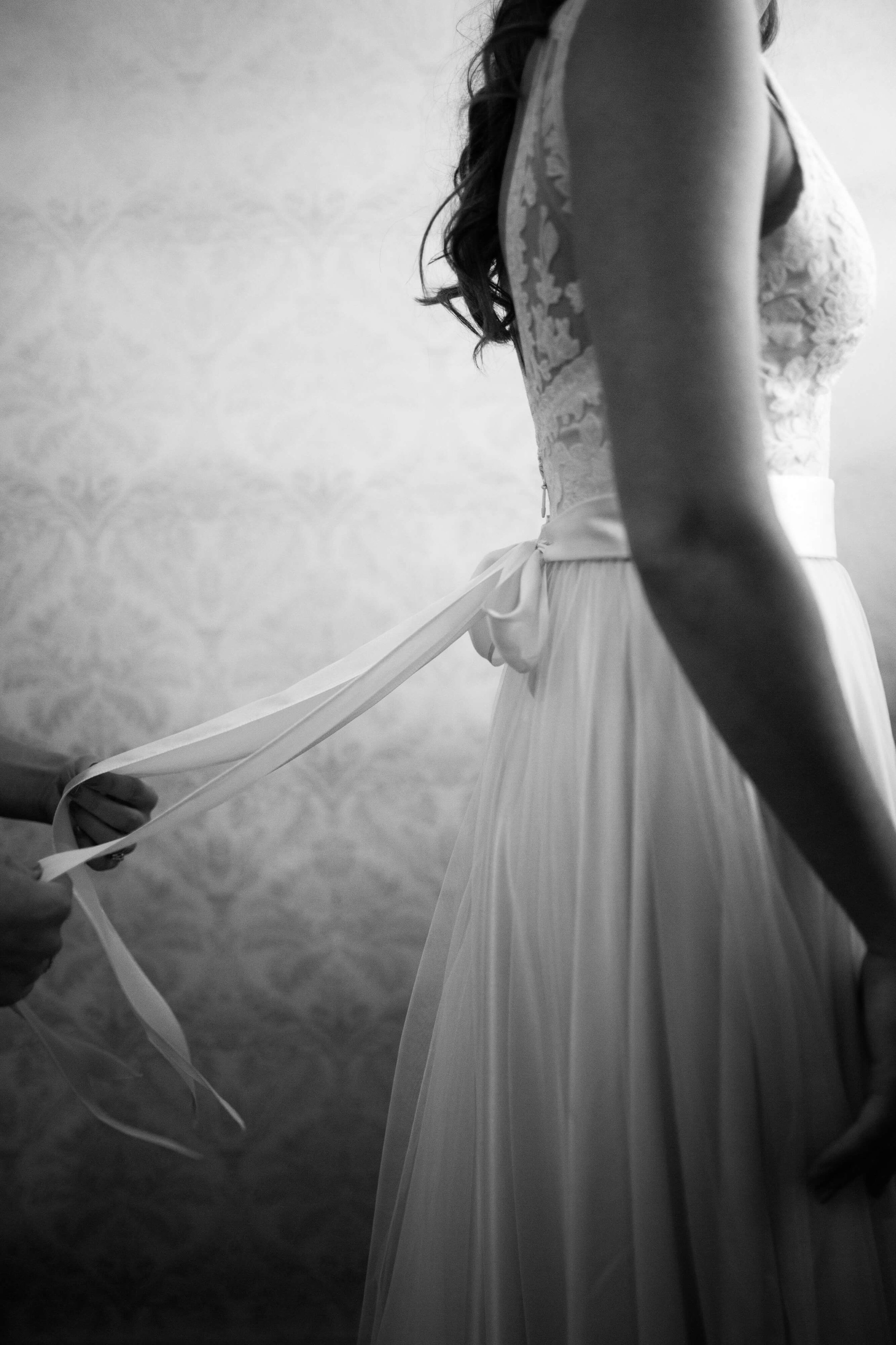 Sixpence Events and Planning | tying ribbon on dress | Studio KH wedding photography