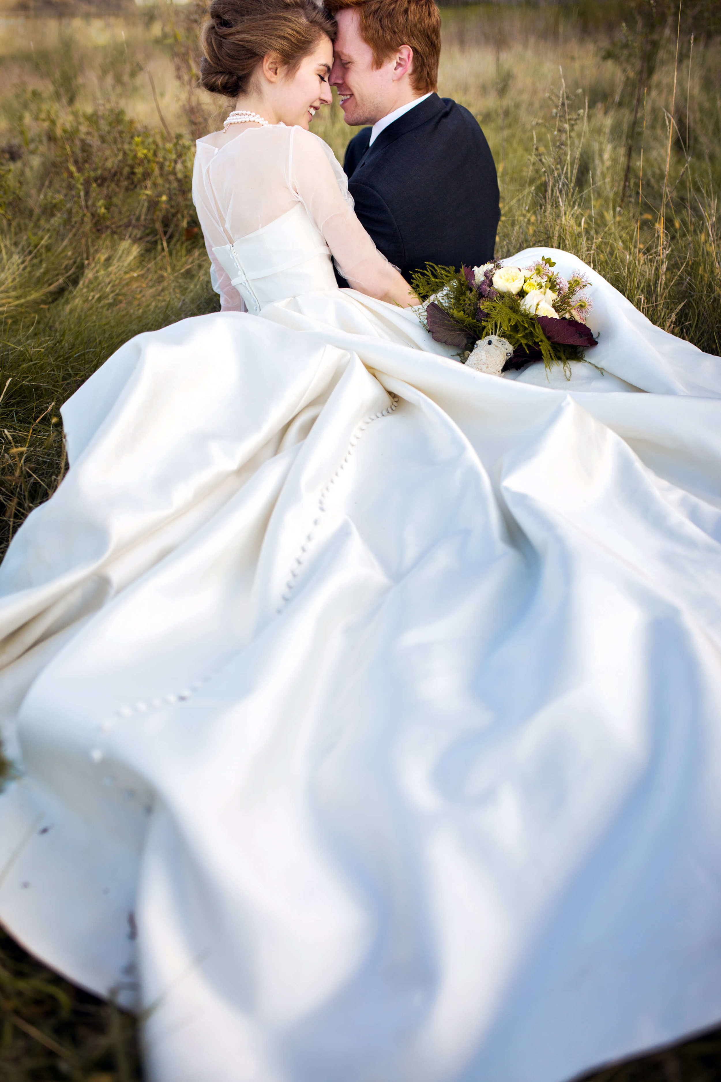 Studio KH Minneapolis wedding photographer | sheer sleeved wedding dress | laying down in the field with large full gown | buttons to the ground | Sixpence Evens & Planning