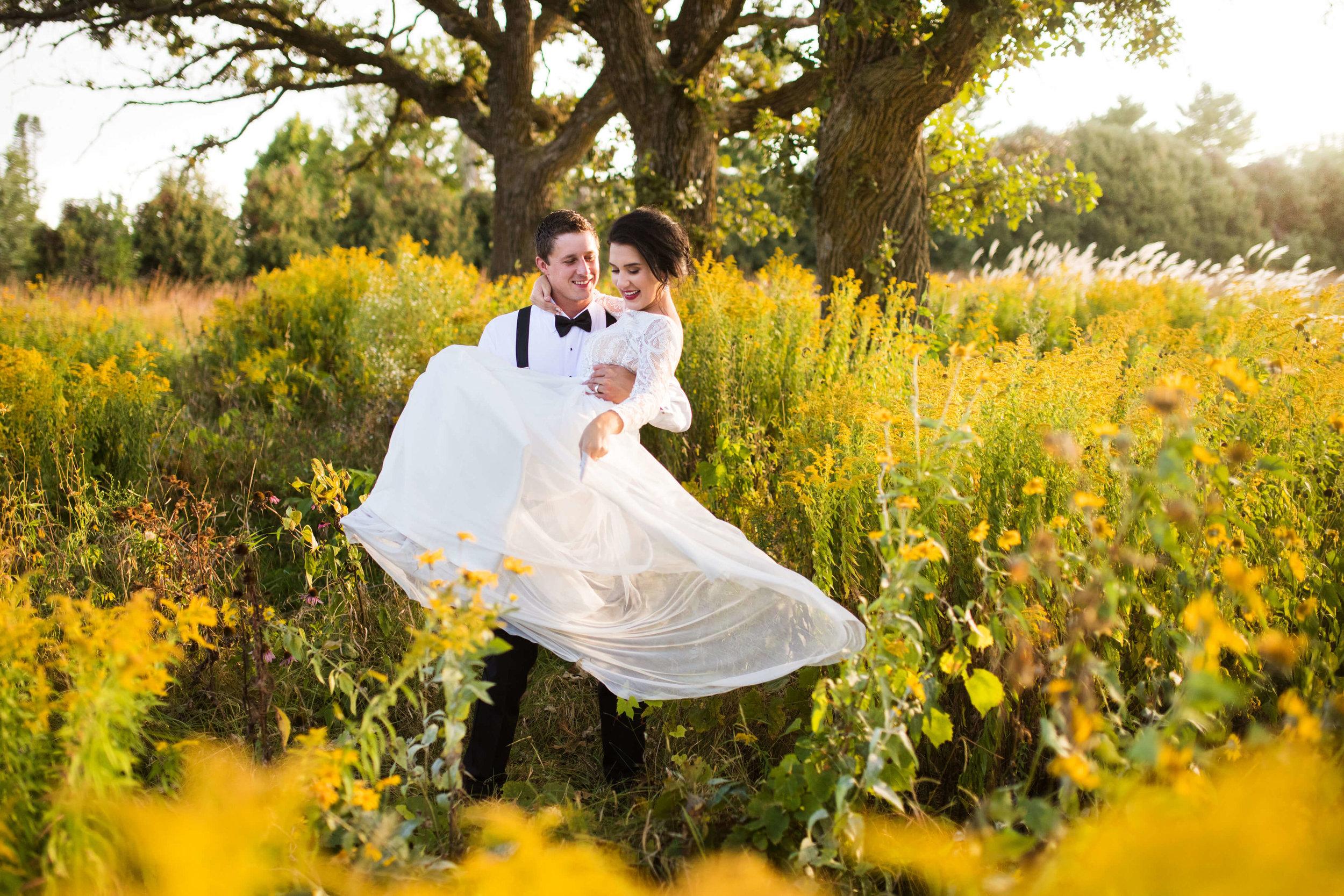 bride and groom in field of yellow | Minnesota wedding photographer Studio KH wedding dress details | wedding blog | Sixpence Events 70 Ways to Photograph Your Wedding Dress.jpg