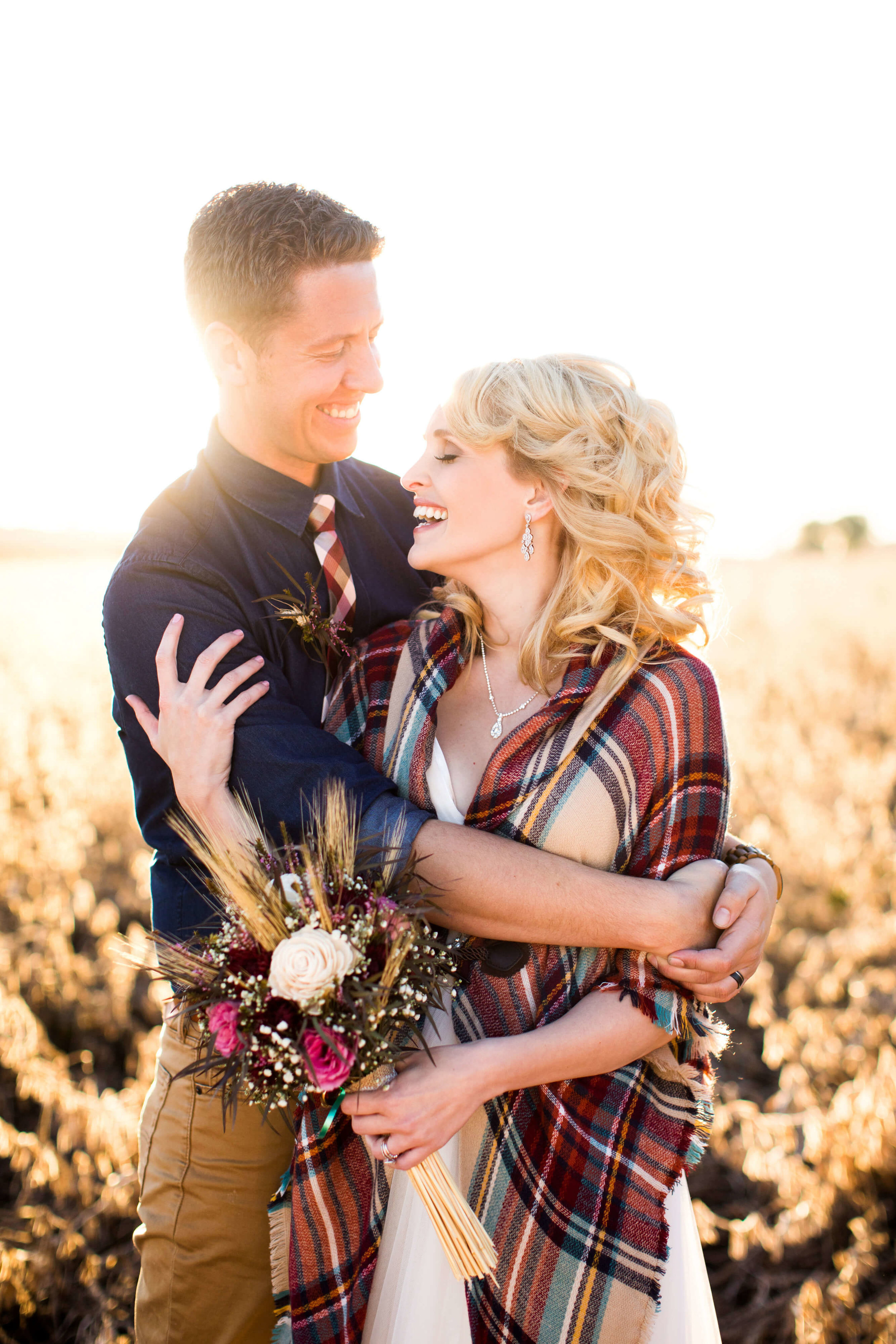 bride wit hharvest plaid shawl and bouquet with wheat | groom in khaki with blue rolled up sleeves and check tie | sunset in the autumn fields | Minnesota wedding photographer Studio KH wedding dress details | wedding blog | Sixpence Events 70 Ways to Photograph Your Wedding Dress.jpg