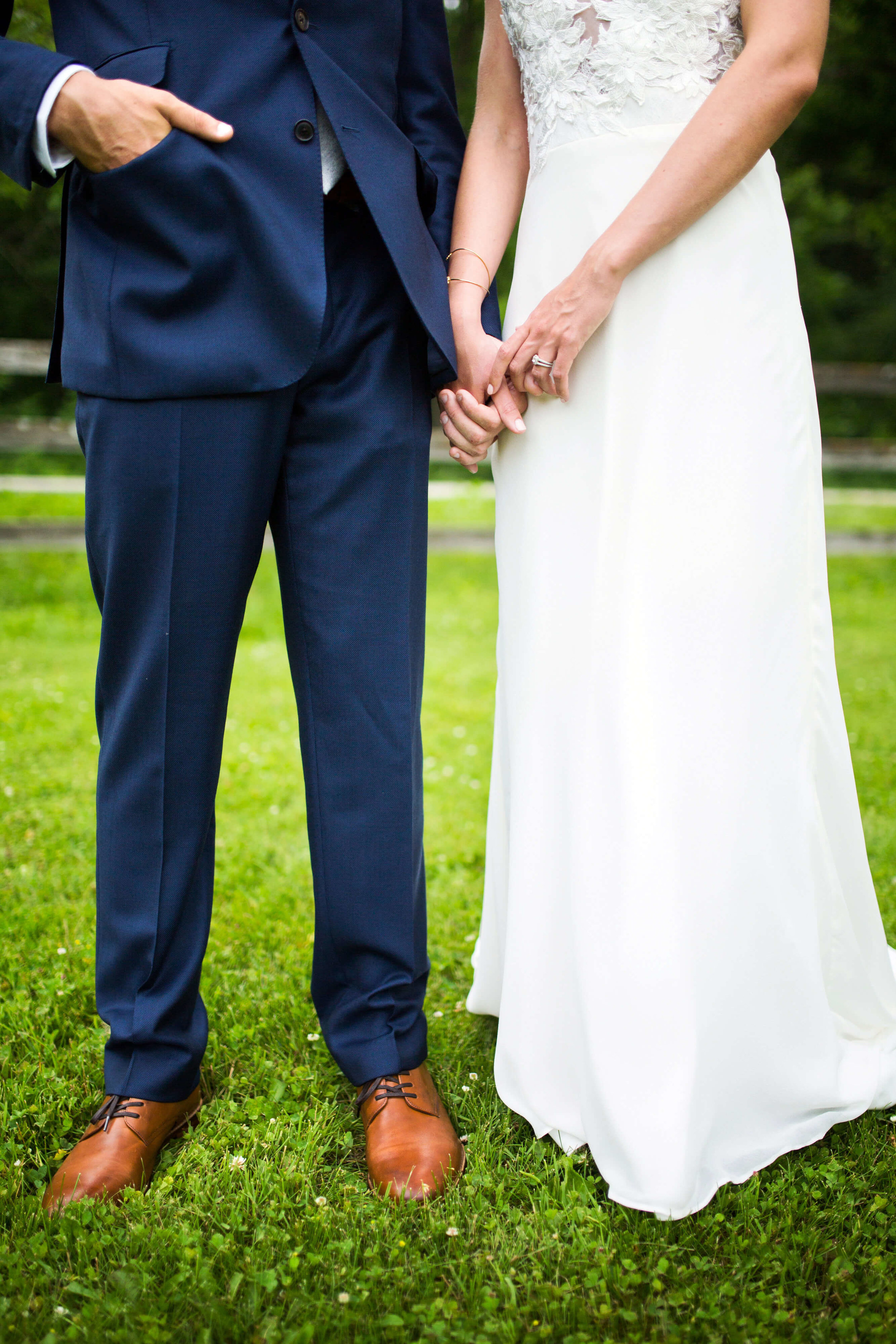 bride and groom holding hands | groom with hand in pocket | Minnesota wedding photographer Studio KH wedding dress details | wedding blog | Sixpence Events 70 Ways to Photograph Your Wedding Dress.jpg