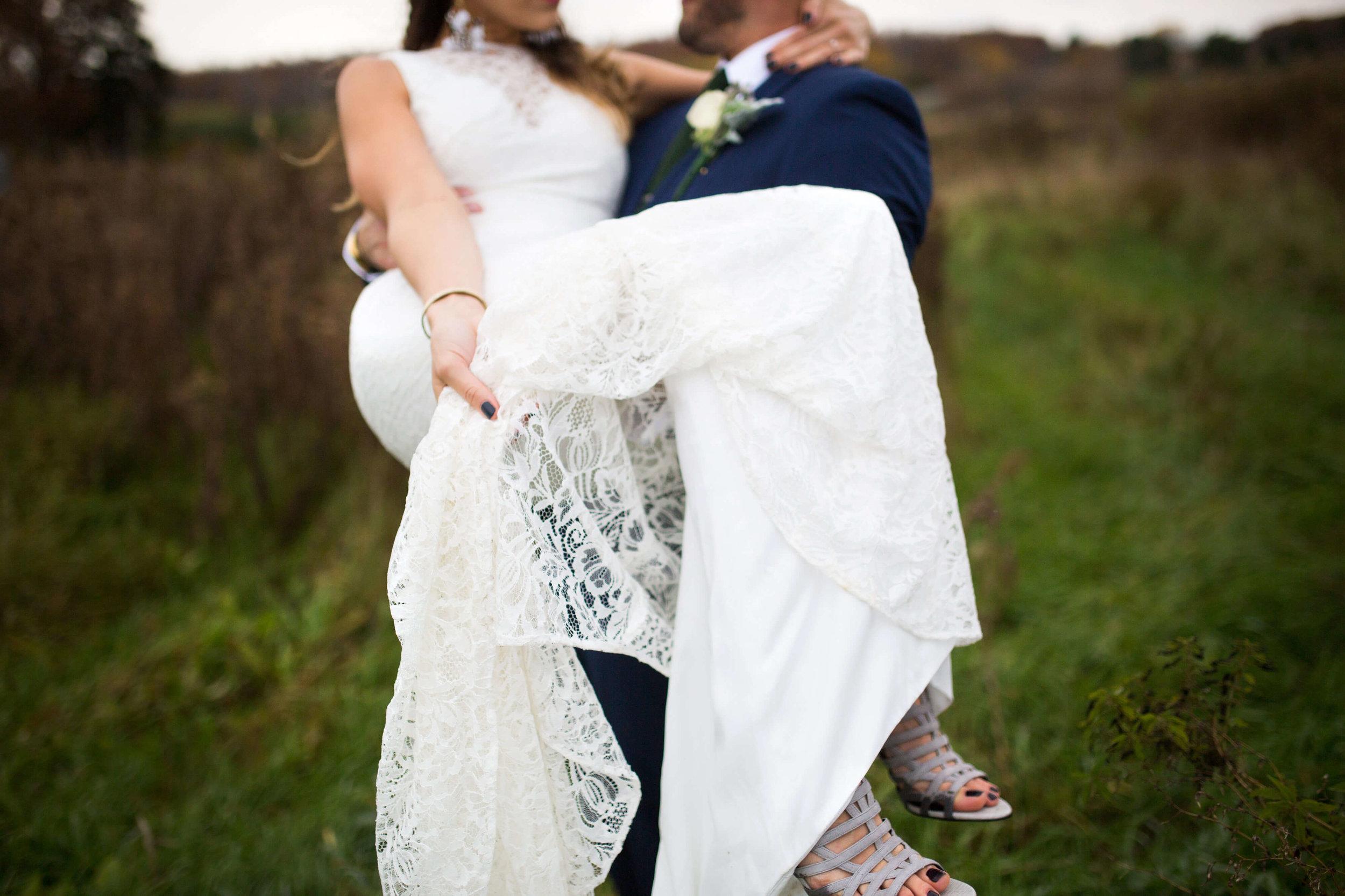 groom carrying bride | Minnesota wedding photographer Studio KH wedding dress details | wedding blog | Sixpence Events 70 Ways to Photograph Your Wedding Dress.jpg