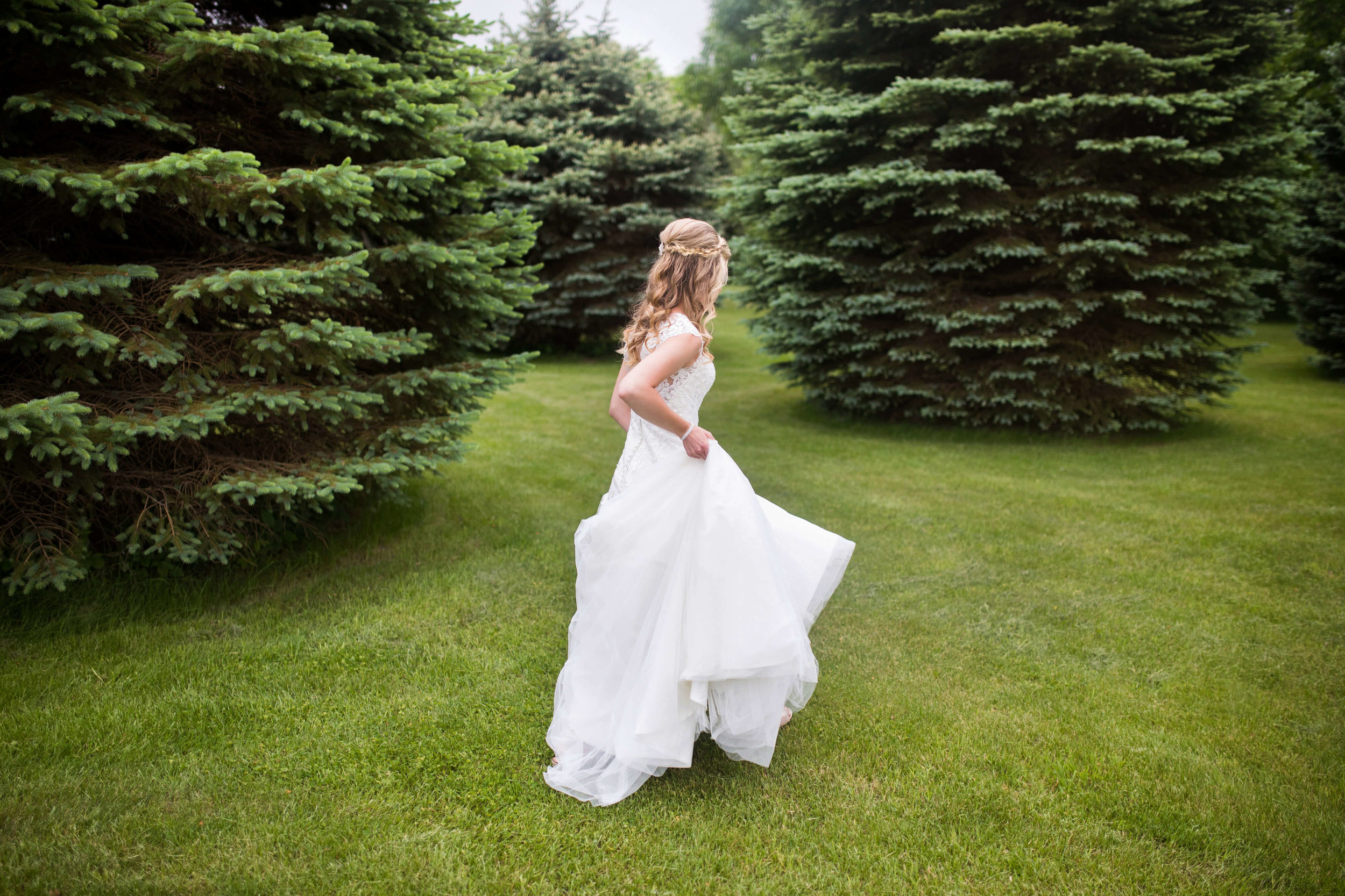 bride walking through the trees | Minnesota wedding photographer Studio KH wedding dress details | wedding blog | Sixpence Events 70 Ways to Photograph Your Wedding Dress.jpg