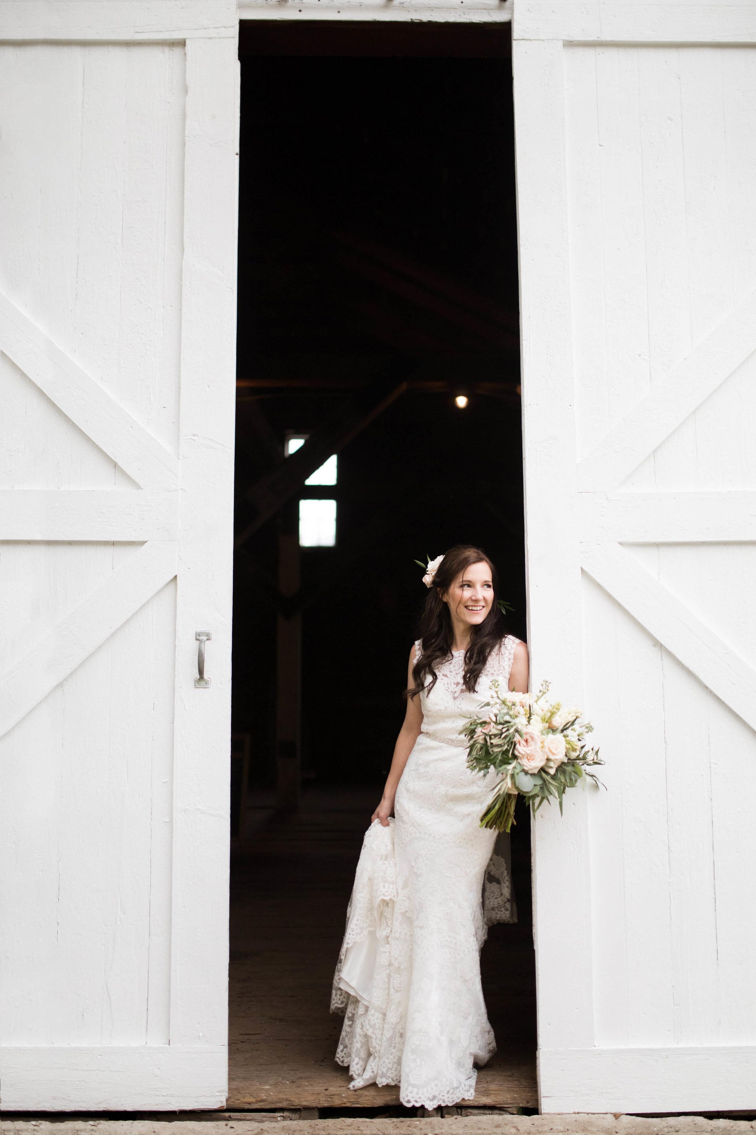 bride standing in the barn doors | Minnesota wedding photographer Studio KH wedding dress details | wedding blog | Sixpence Events 70 Ways to Photograph Your Wedding Dress.jpg