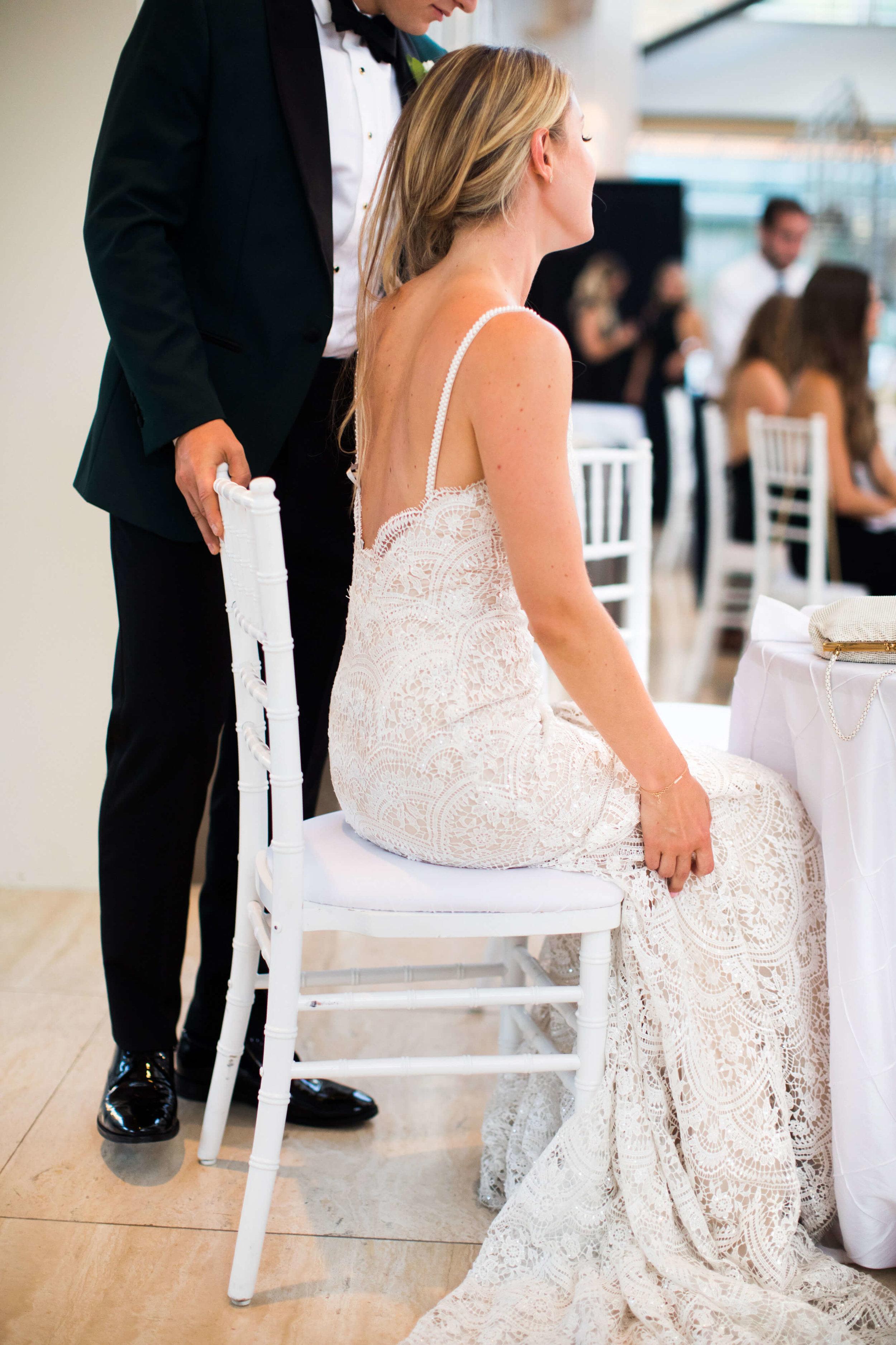 groom pushing bride into table with chair chiavari | Minnesota wedding photographer Studio KH wedding dress details | wedding blog | Sixpence Events 70 Ways to Photograph Your Wedding Dress.jpg