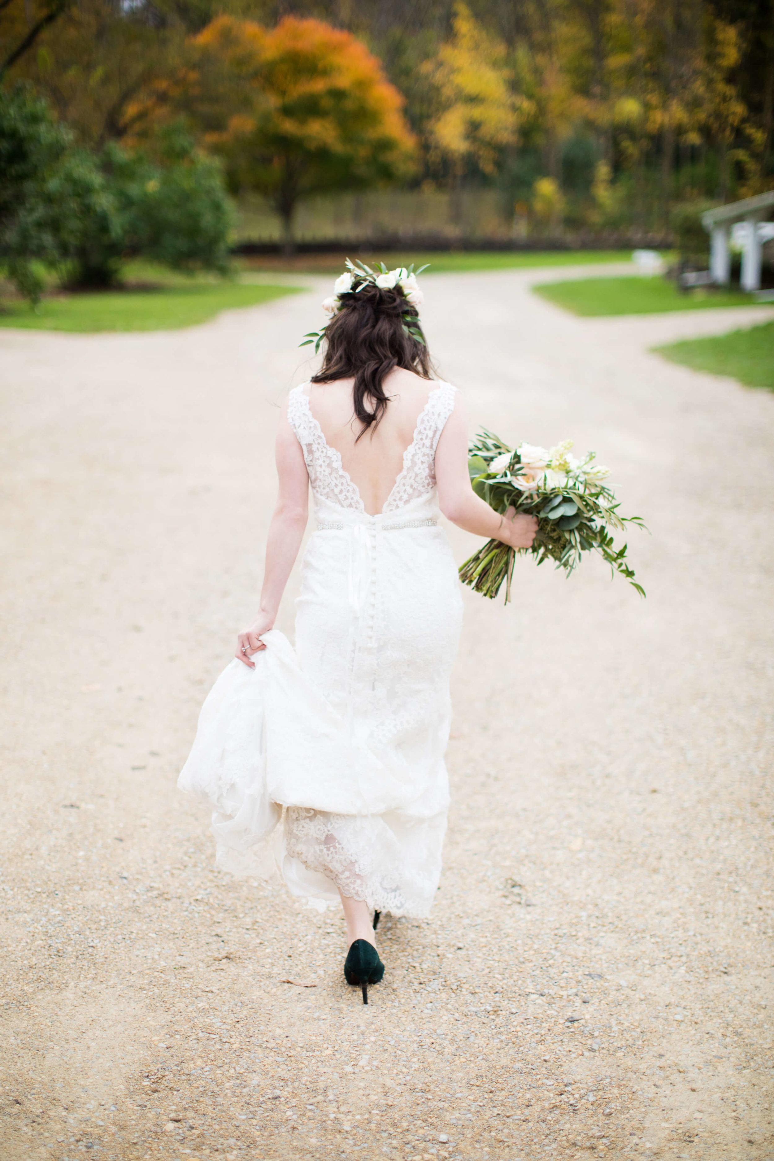 bride walking down the road | v back lace detail | Minnesota wedding photographer Studio KH wedding dress details | wedding blog | Sixpence Events 70 Ways to Photograph Your Wedding Dress.jpg