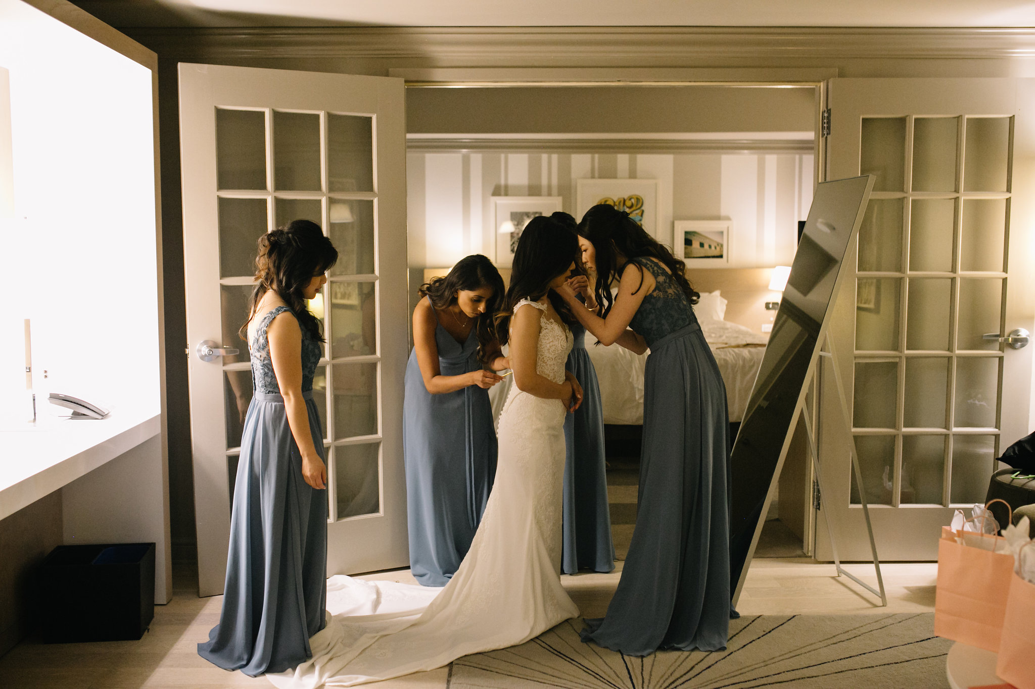 bridesmaids helping you into your dress, Whims and Joy Minneapolis photographer :: Sixpence Events & Planning Minnesota wedding planner :: Nicollet Island Pavilion.jpg