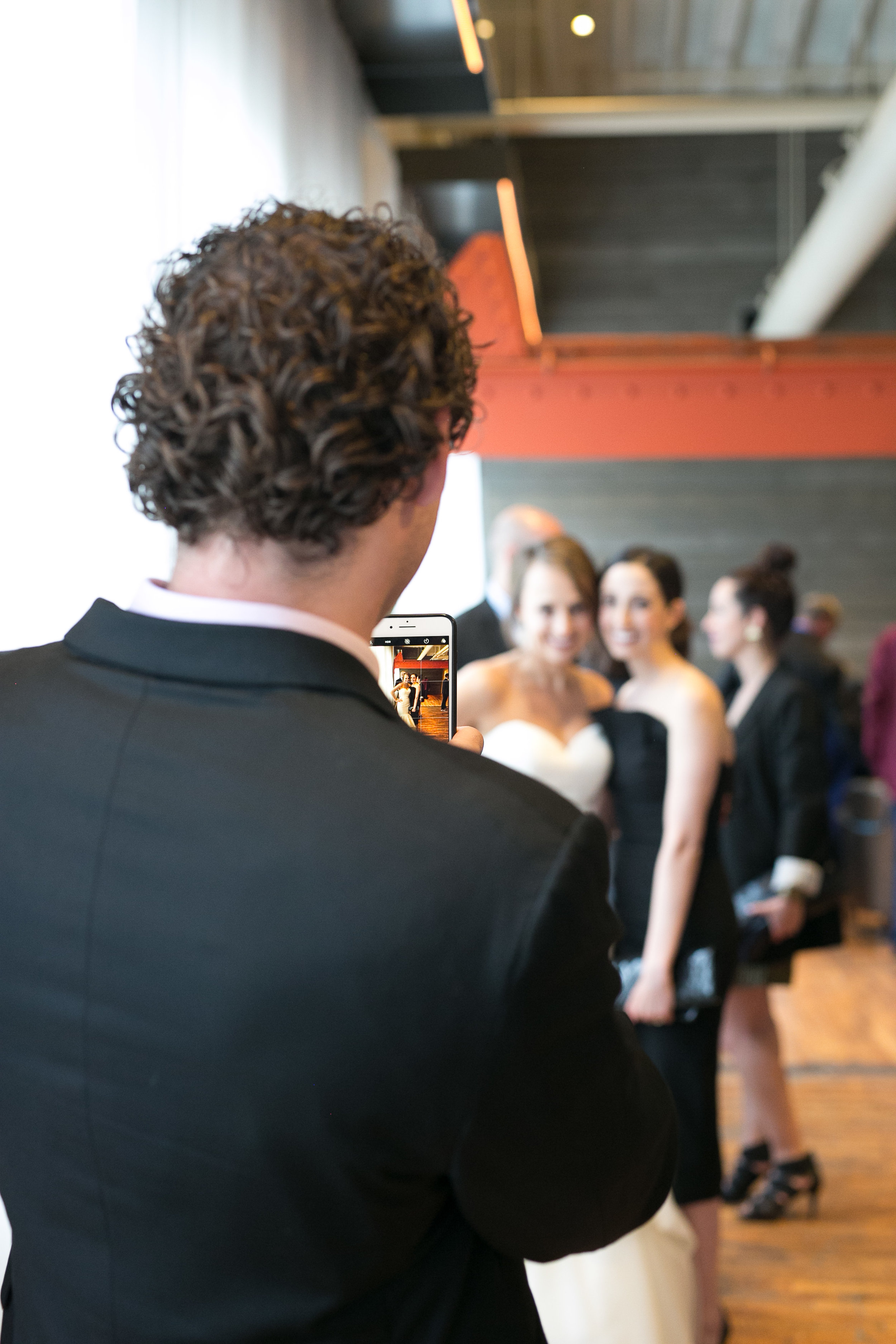 guest taking a picture of the bride with her friend | Alice HQ Photography | Machine Shop Minneapolis | Sixpence Events and Planning wedding planner.JPG