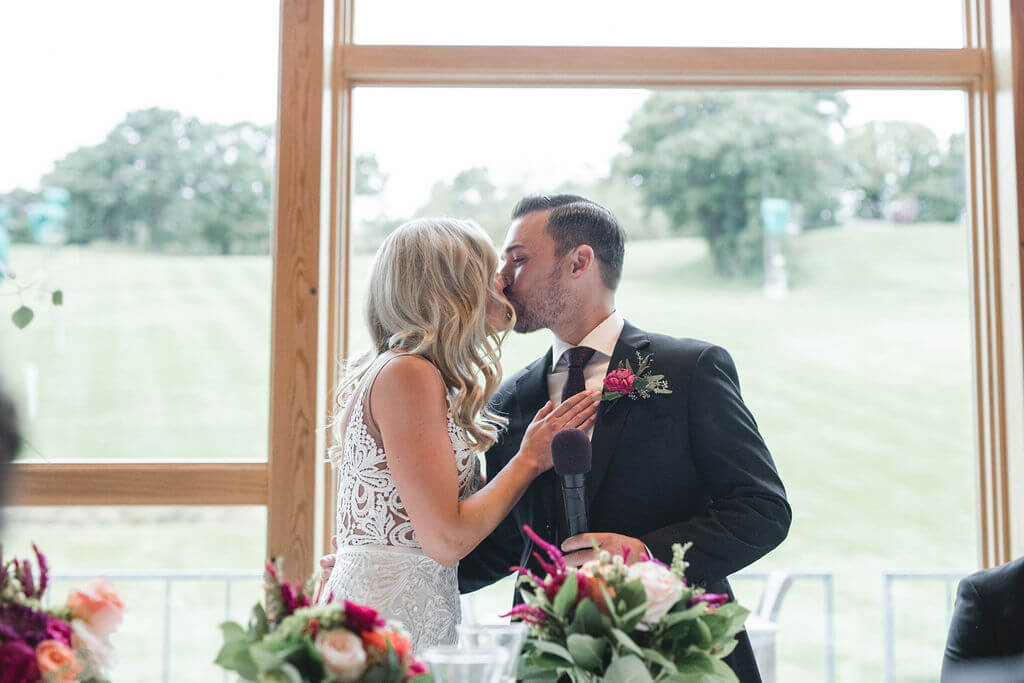 Ashley and Tom | Mariah Brink Photo | Hyland Hills Wedding | Sixpence MN wedding planner | dinner kiss at the head table