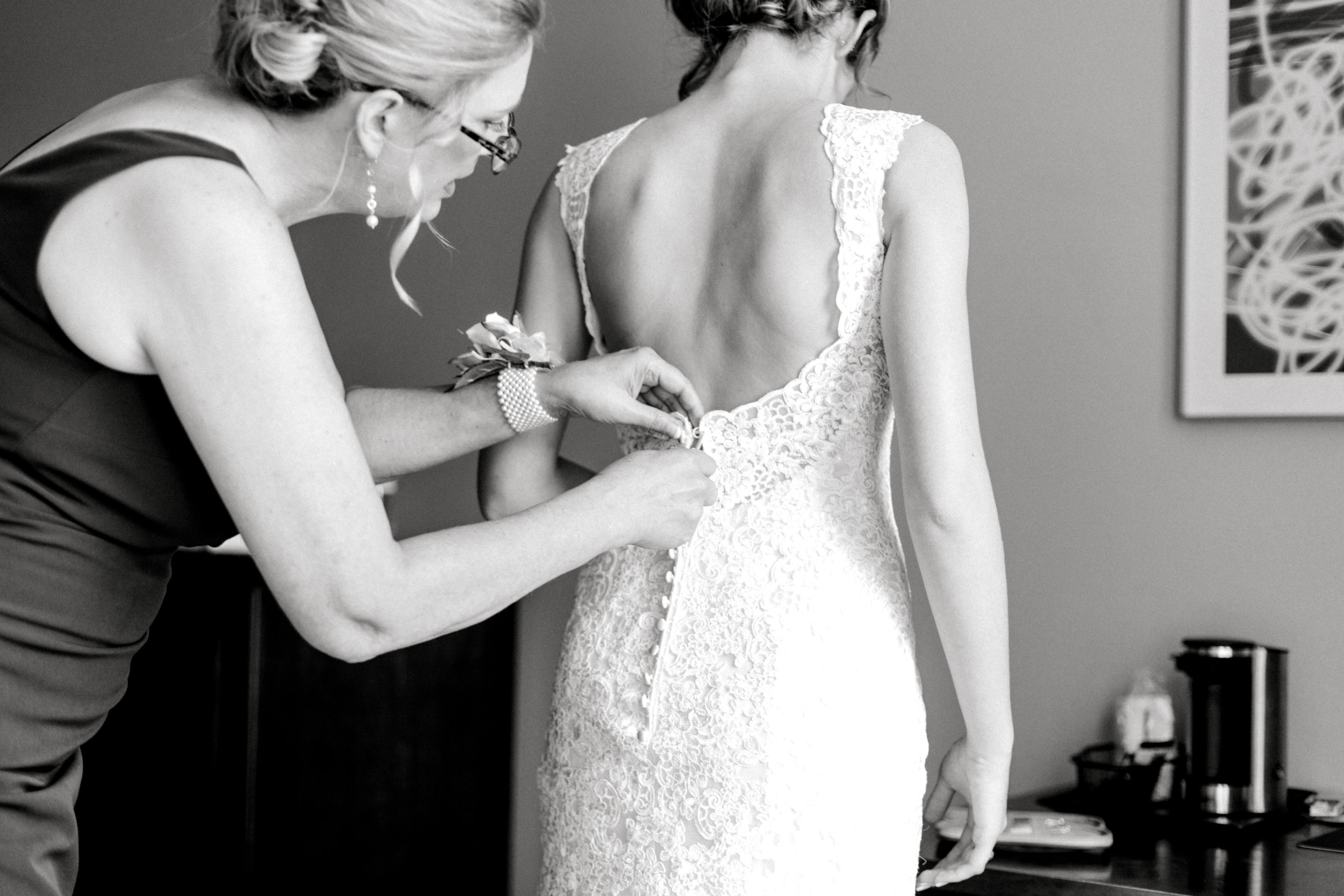 bride getting ready, buttoning dress | Lauren Baker Photography Minneapolis wedding photographer | Sixpence Events blog post Wedding Photography Tips