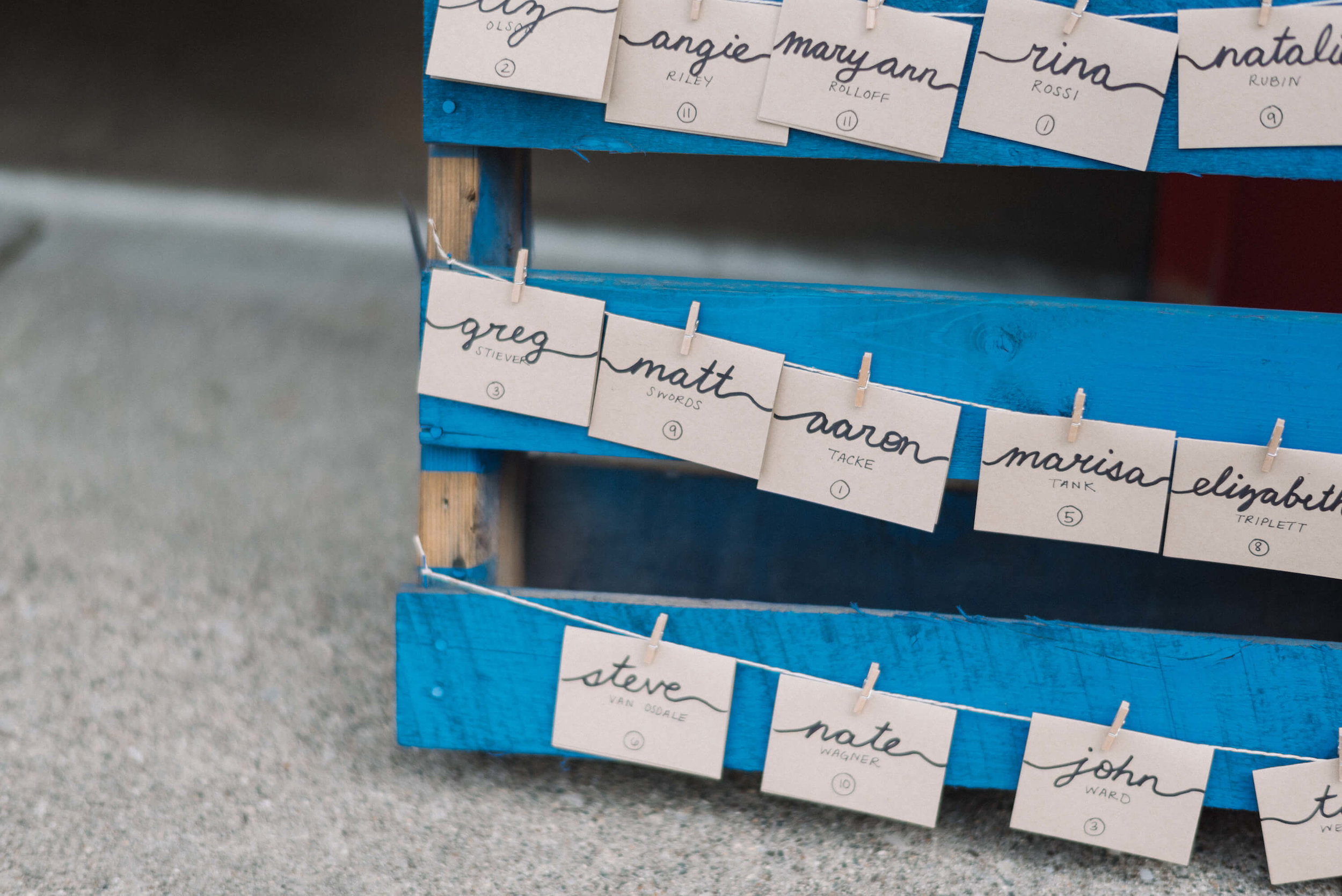 Palette board seating chart with tiny clothespins | Jonny and Liz Minnesota Wedding Photographers | Sixpence day of coordinating at Gale Woods farm venue near the lake.JPG