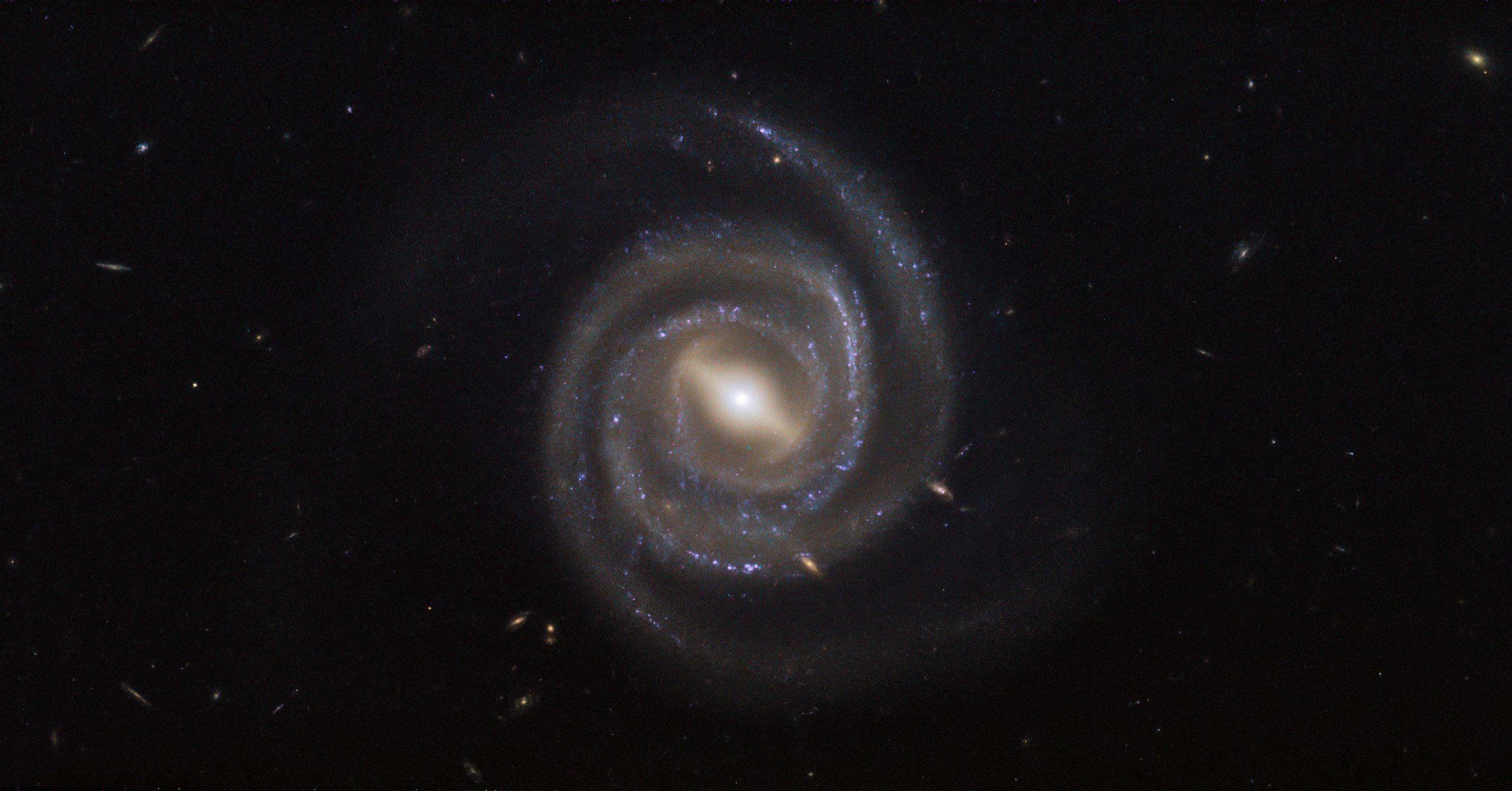 Hubble's Barred and Booming Spiral Galaxy. UGC 6093 is something known as a barred spiral galaxy — it has beautiful arms that swirl outwards from a bar slicing through the galaxy's center. From NASA Hubble images at https://www.nasa.gov/mission_pages/hubble/multimedia/index.html.