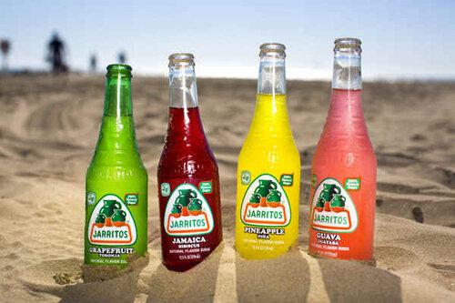 Four Jarritos soft drink bottles in a beach sand