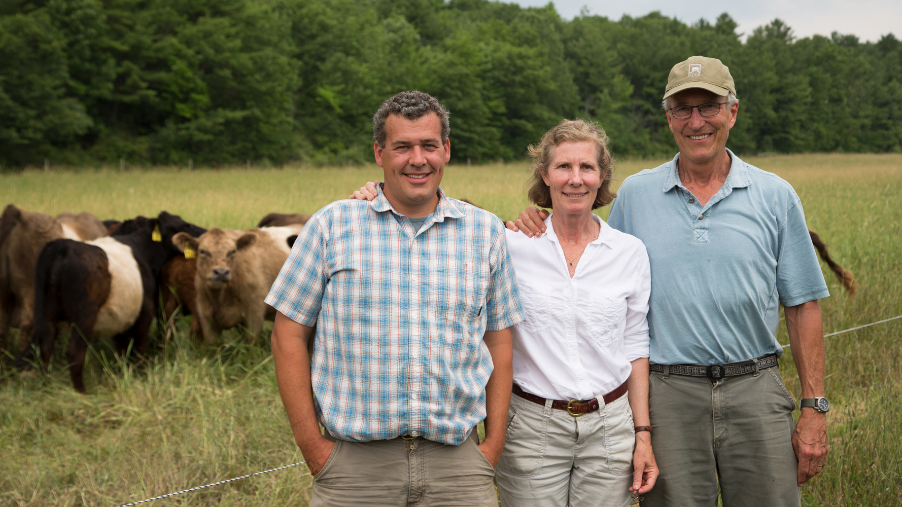 Ed, Diana and Peter standing in front of our herd of Belted Galloways.
