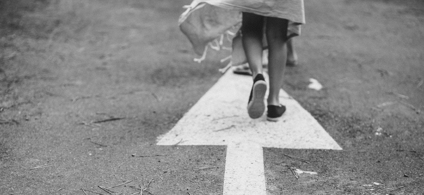 woman-walking-arrow-street-black-white.jpeg