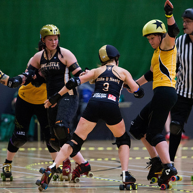 Sarah McMillan skipping up the inside line to avoid a hit from Anita B Nasty; photo courtesy of  Dave Moore .
