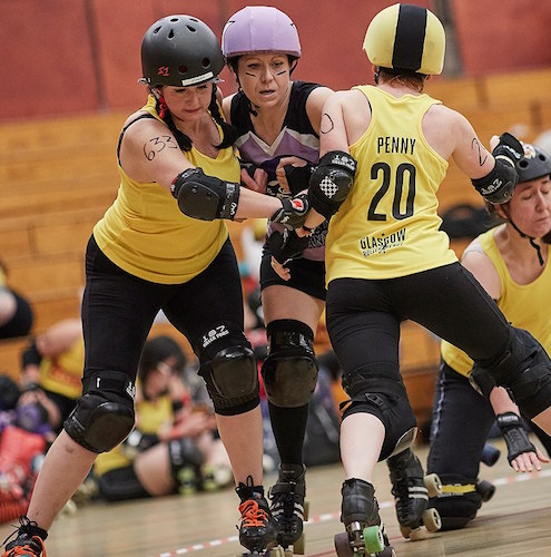 Stinger Belle & Penny Pinch'er holding back the Halifax jammer; photo courtesy of  Roller Derby on FIlm .
