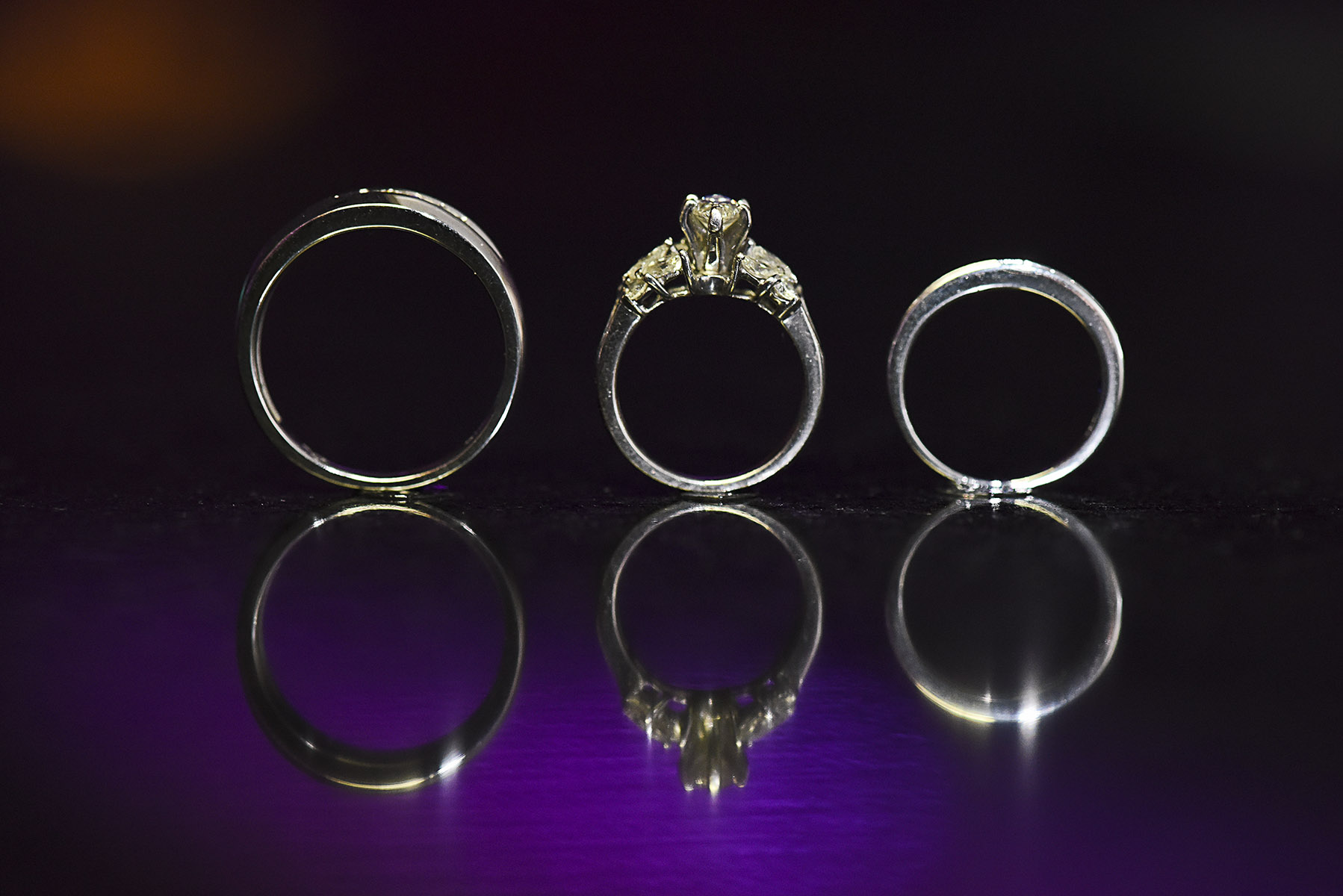 Wedding ring photography done during dance & reception using macro lens,led light, and glue dots. Any reflective surface works great for these detail shots. Add some interesting lighs and bam!