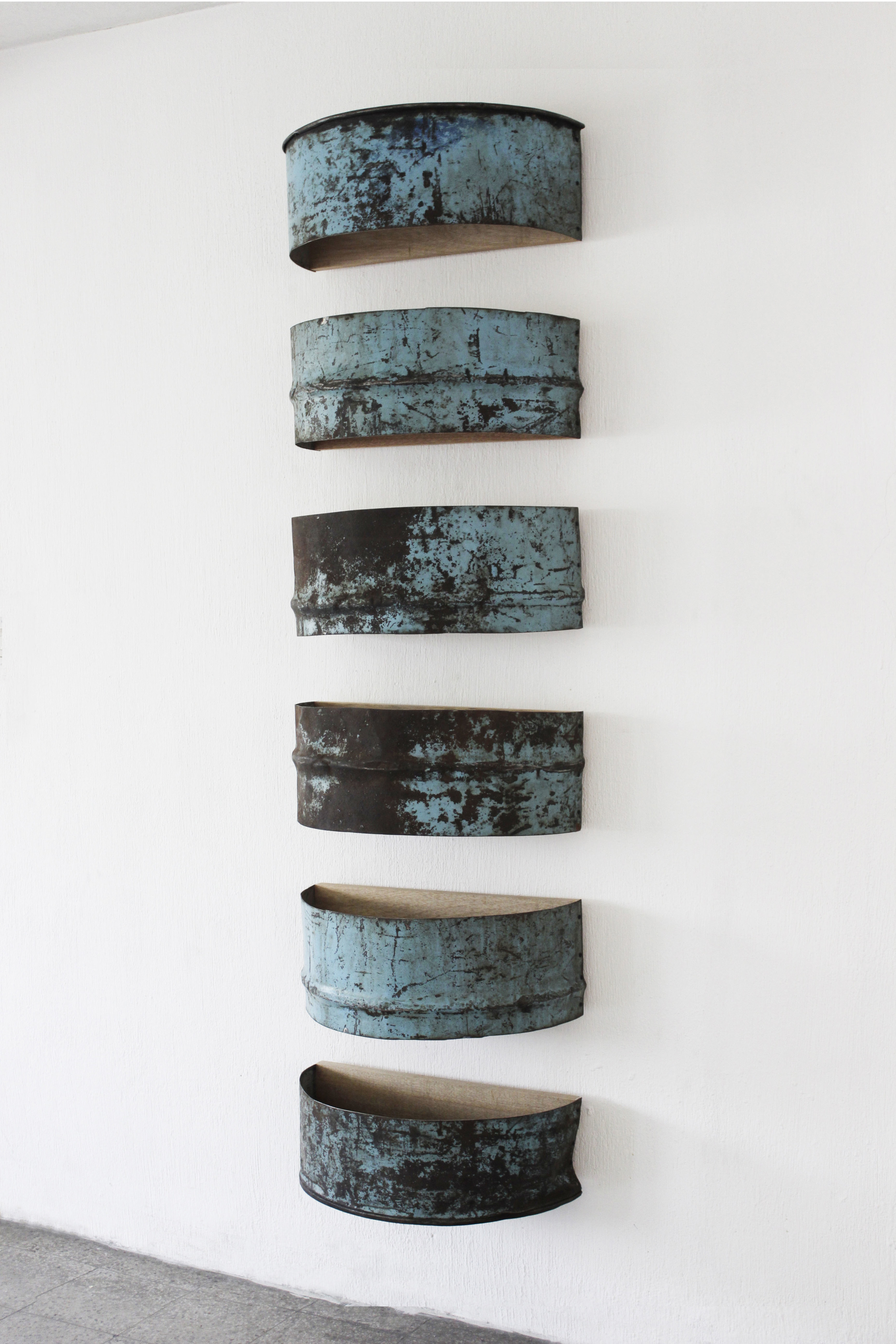 Repetition No. 3, 2014  Found iron barrel fragmentsassembledonwood panels, protected with acryloid.  202 x 58 x 31 cm. [79 1/2 x 22 13/16 x 12 3/16]  Photo by Diego Sagastume