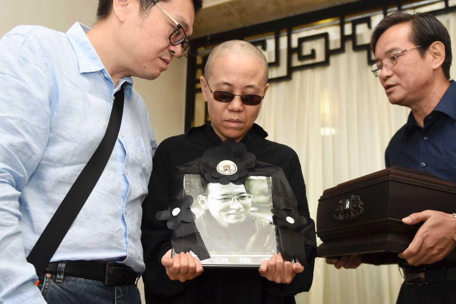 Liu Xia holds a portrait of Liu Xiaobo during his funeral .AP: Shenyang Municipal Information Office