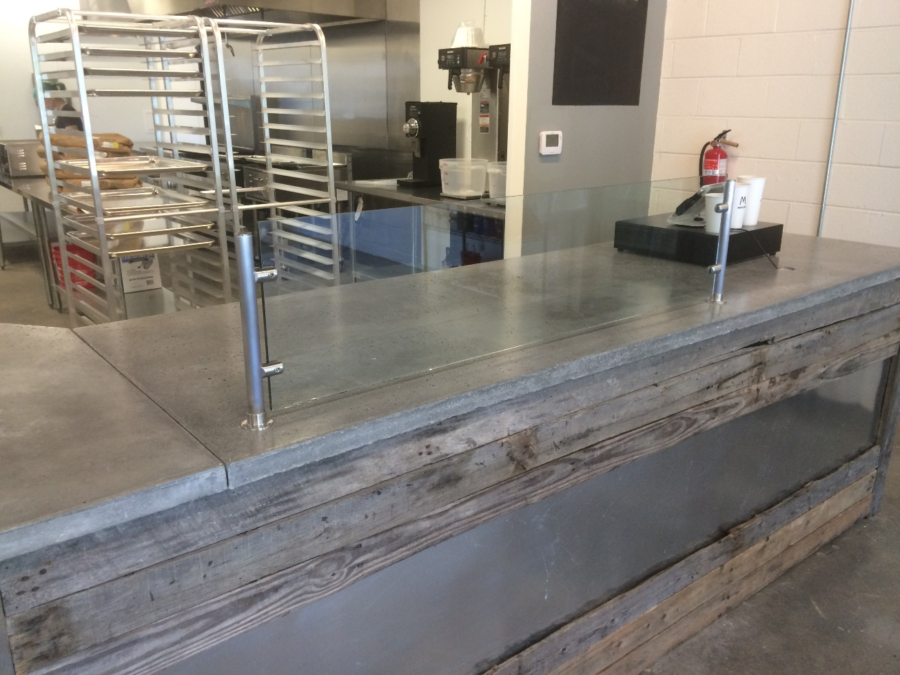 Reclaimed wood and metal wrapped bar with cement countertops.