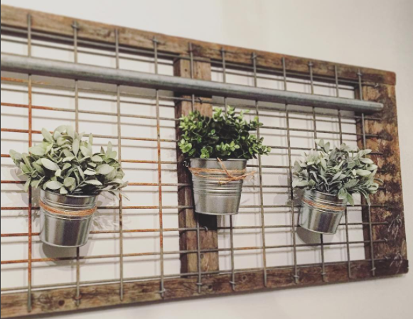 Hung with to wall with wall anchors. Galvanized tins are hung with twine and S hooks.