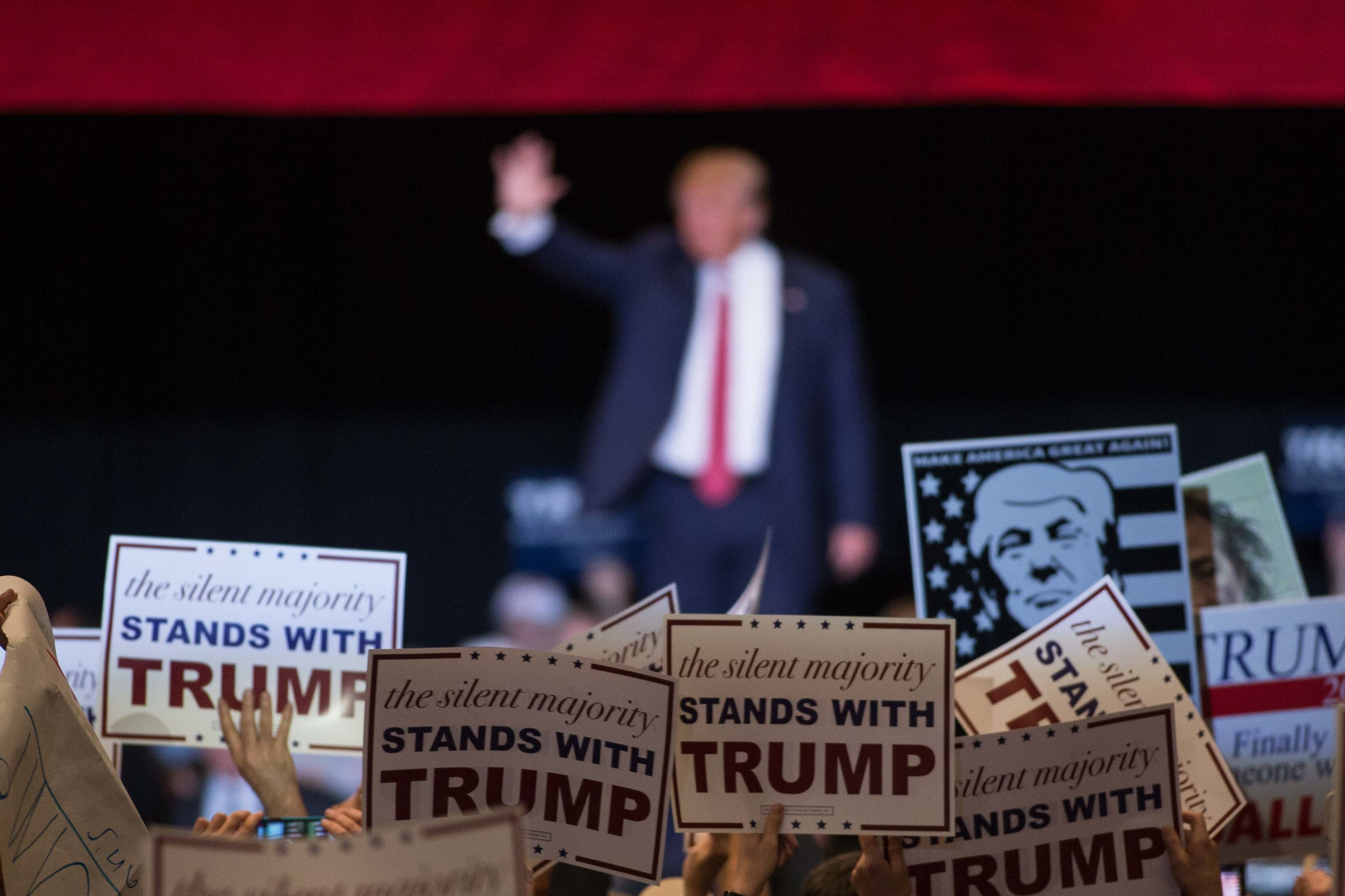 People hold up signs as Republican presidential candidate Donald Trump walks on stage during a campaign rally at the Macon Centreplex, Monday, Nov. 30, 2015, in Macon, Ga. (AP Photo/Branden Camp)