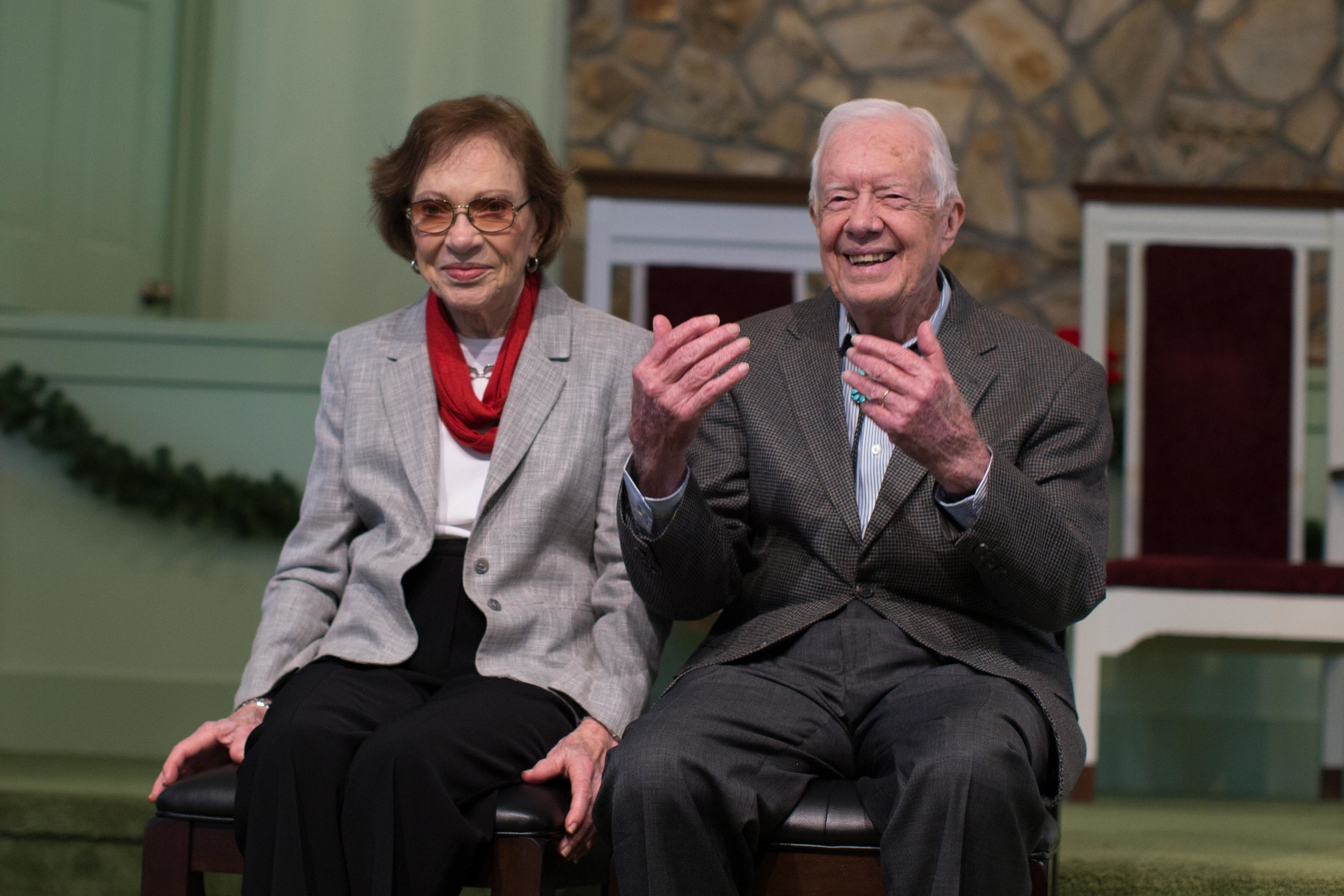 """Former President Jimmy Carter, right, sits with his wife, Rosalynn, as they wait to pose for photos with guests at Maranatha Baptist Church, Sunday, Dec. 13, 2015, in Plains, Ga. A recent MRI showing no cancer on Jimmy Carter's brain is """"very positive"""" news for the former president but will not end his medical treatment, doctors said. Carter, 91, announced on Dec. 6 that doctors found no evidence of the four lesions discovered on his brain this summer and no signs of new cancer growth. (AP Photo/Branden Camp)"""