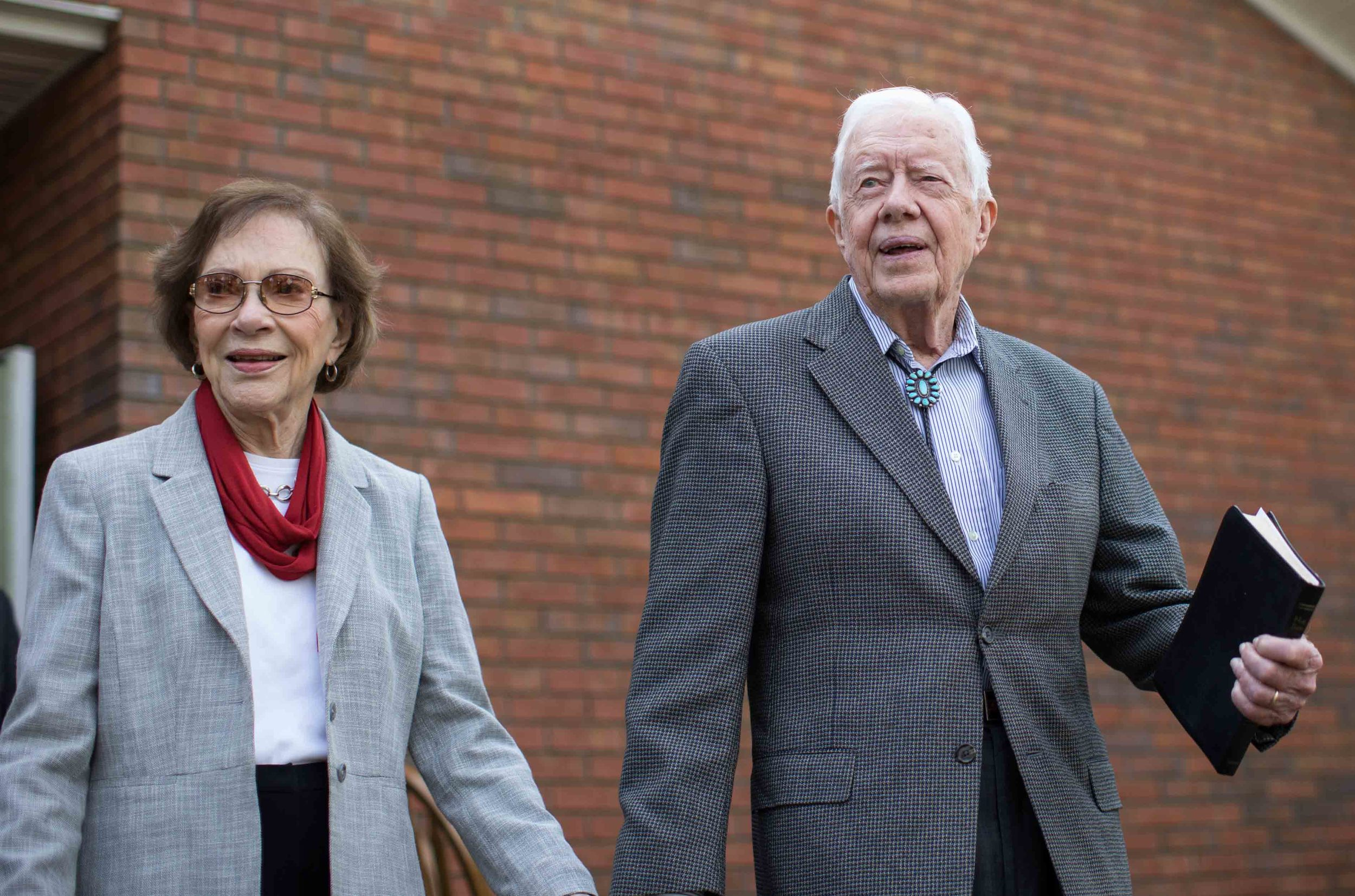 """Former President Jimmy Carter walks with his wife Rosalynn after teaching Sunday School class at Maranatha Baptist Church Sunday, Dec. 13, 2015, in Plains, Ga. A recent MRI showing no cancer on Jimmy Carter's brain is """"very positive"""" news for the former president but will not end his medical treatment, doctors said. Carter, 91, announced Dec. 6 that doctors found no evidence of the four lesions discovered on his brain this summer and no signs of new cancer growth. (AP Photo/Branden Camp)"""
